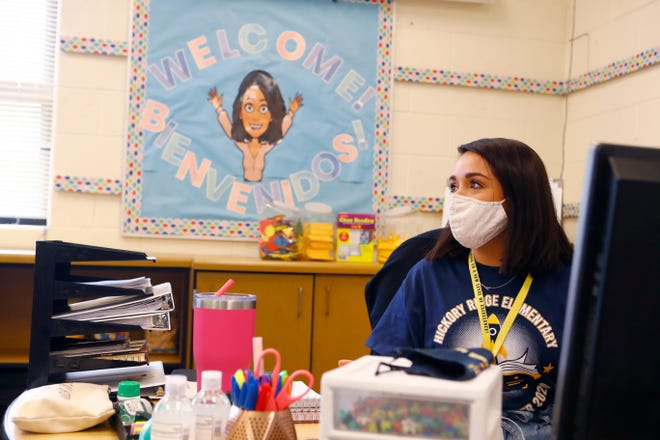 A masked teacher sits at her desk at a Memphis school.