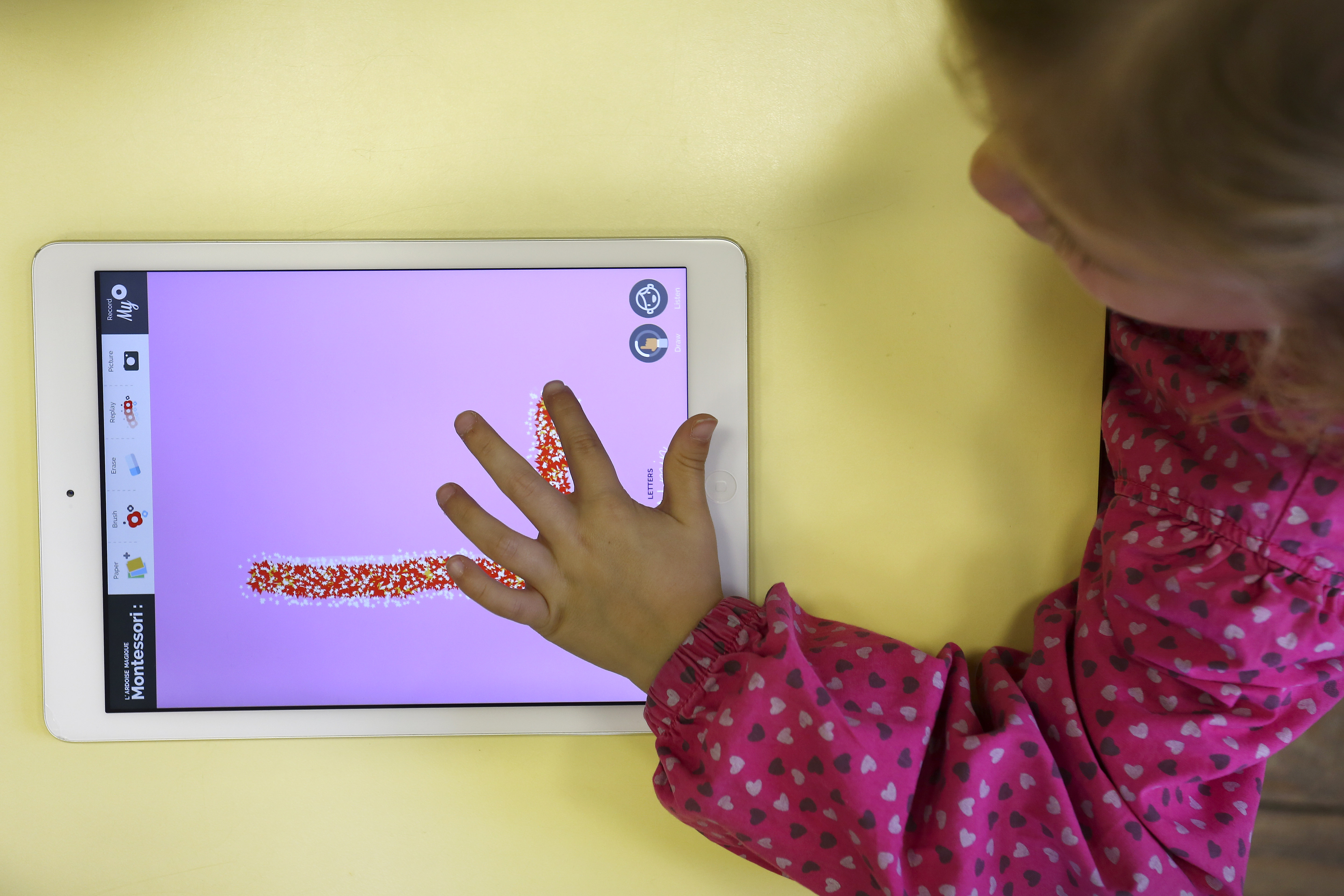 Young girl uses a digital tablet to draw letters (here, an L).