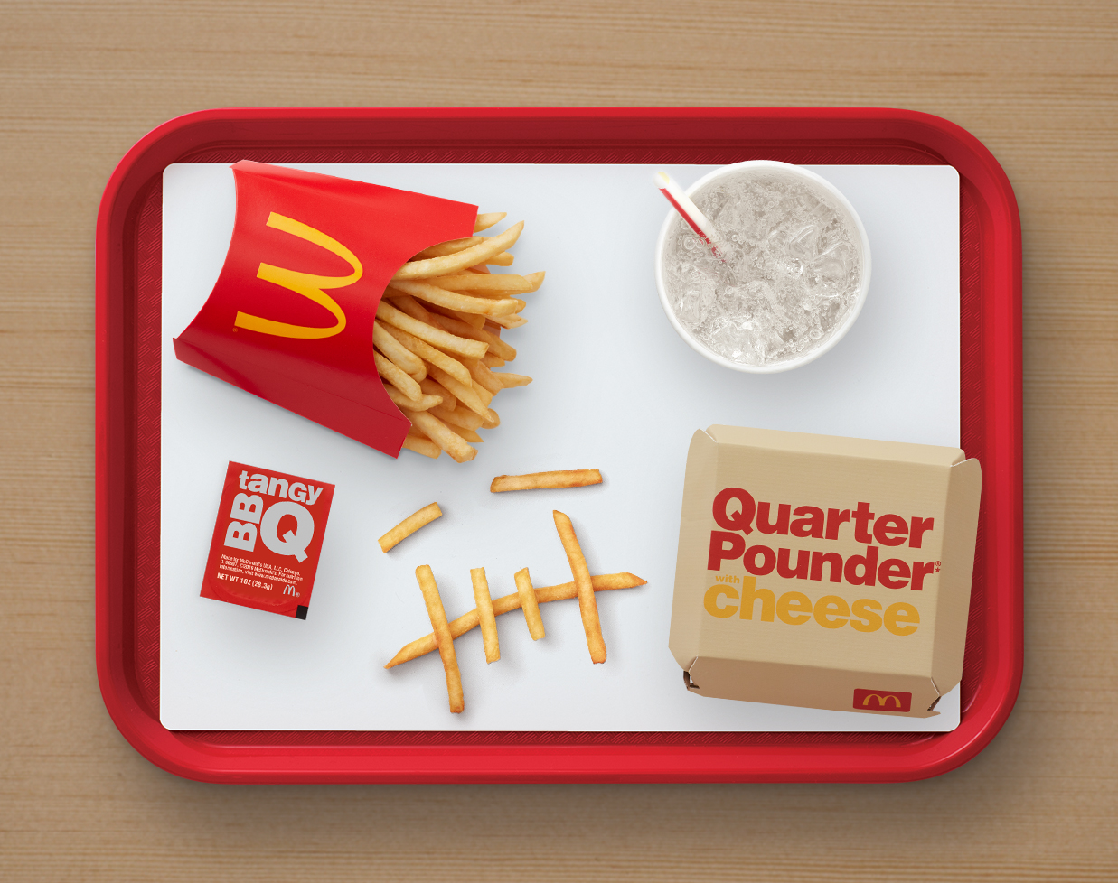 An overhead shot of a quarter pounder with cheese box, fries, bbq sauce and a sprite at McDonald's