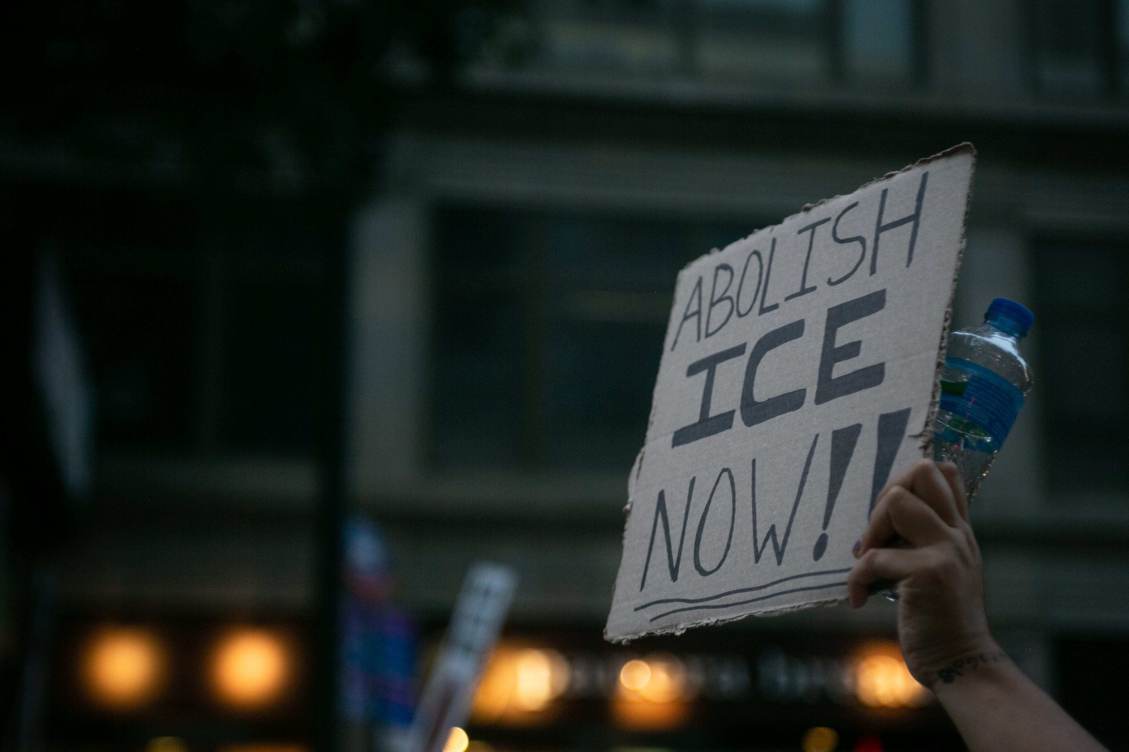 """A hand gripping a bottle of water holds up a sign that reads """"Abolish ICE Now"""" in all caps"""