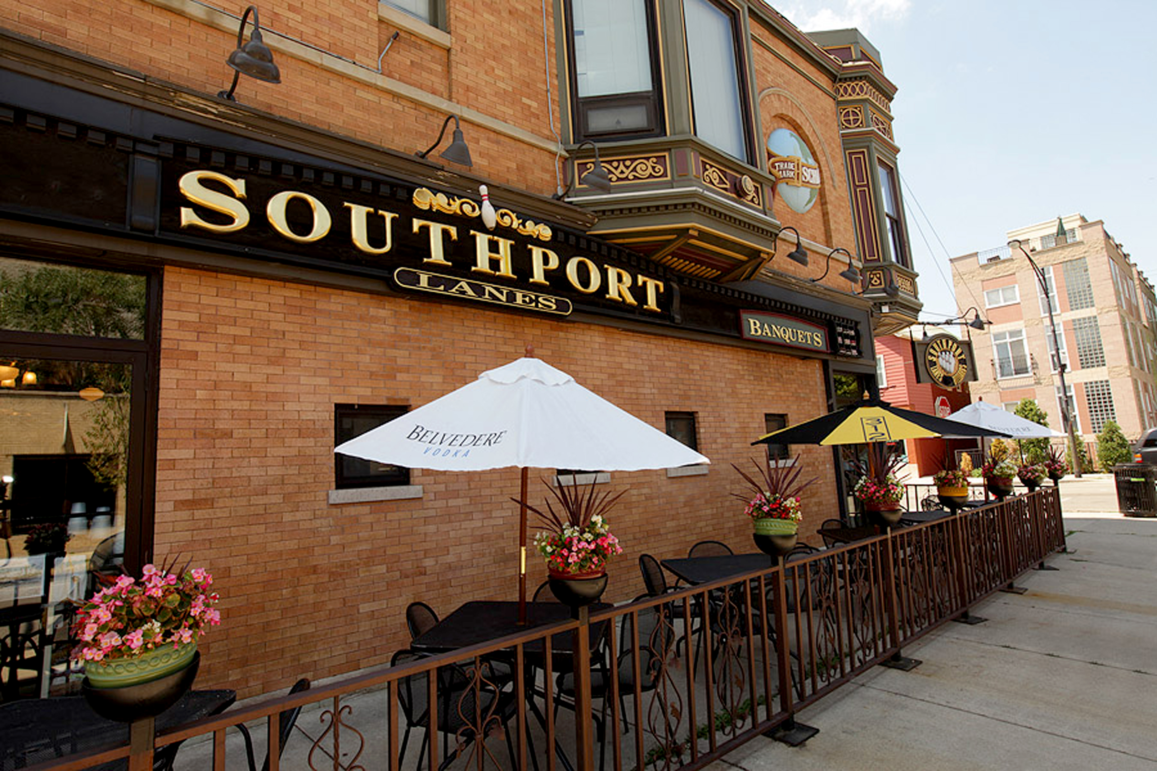 "A large brick bar with gold lettering that reads ""Southport Lanes."""