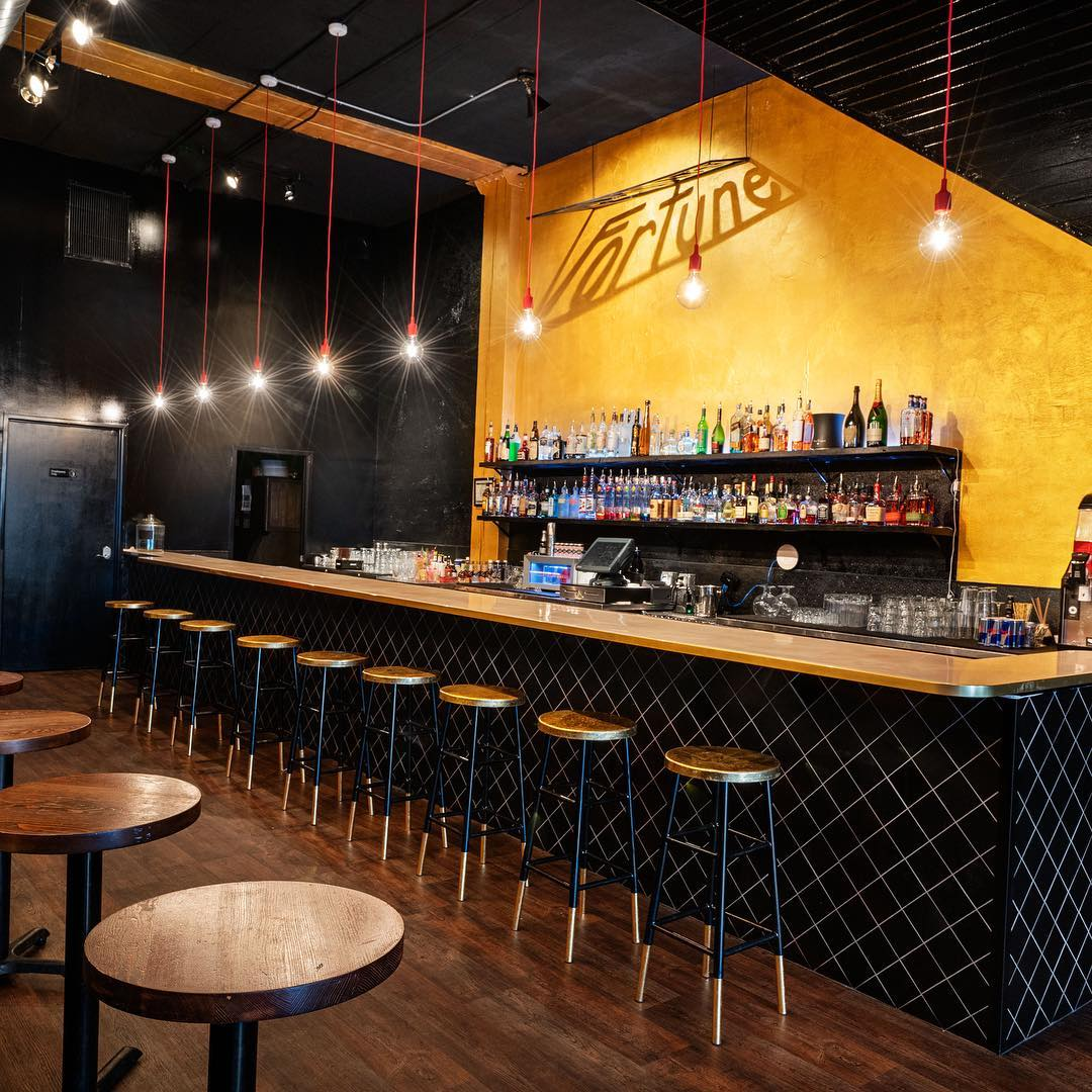 The bar at Fortune, with its gold backdrop, cocktails, and wooden stools