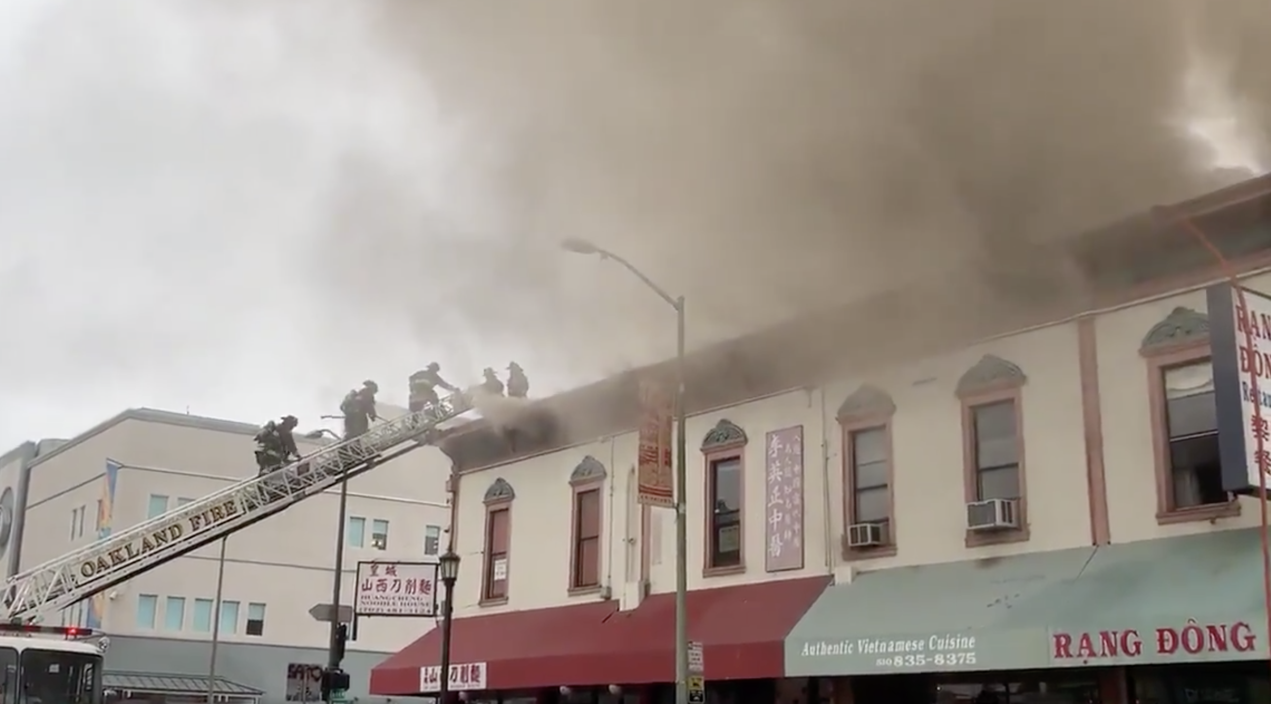 Firefighters climb onto the roof of the Chinatown building, with smoke billowing