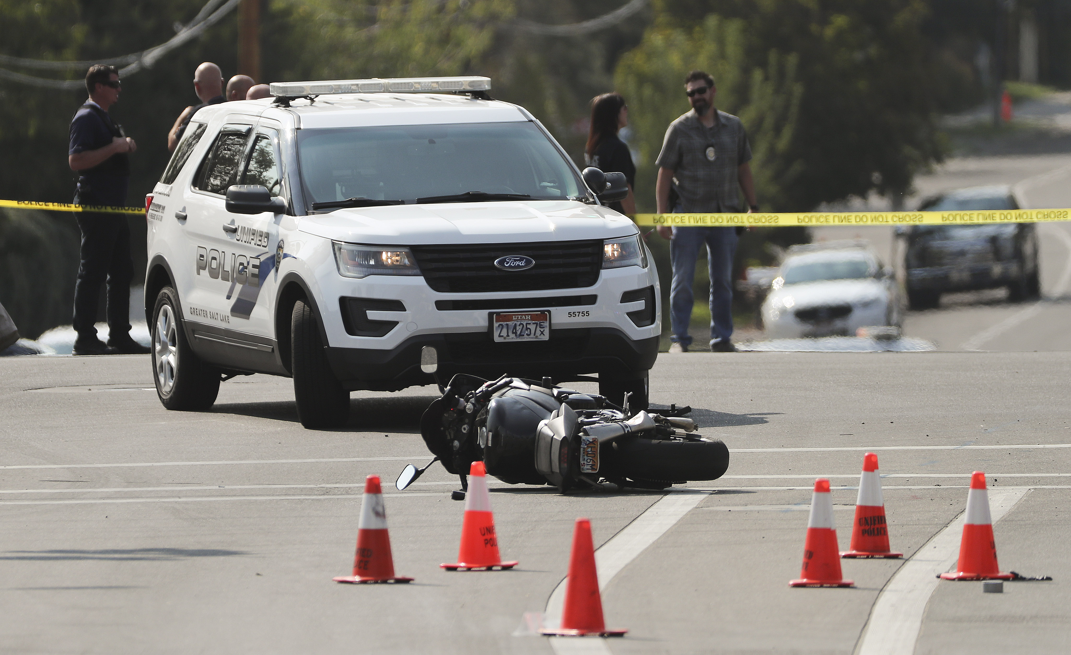 A motorcycle is pictured in the road a members of law enforcement investigate an officer-involved shooting at 4500 South and 2300 East in Holladay on Thursday, Sept. 17, 2020.