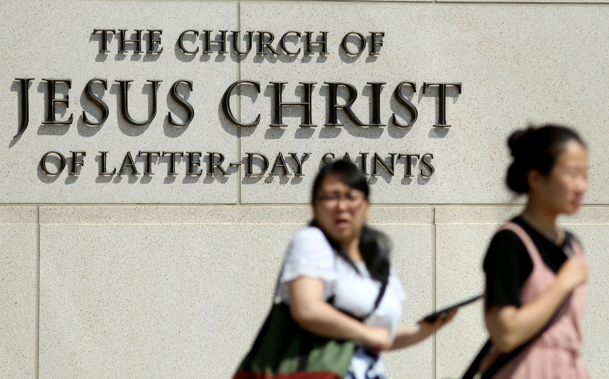 """Pedestrians walk past the Church History Building in Salt Lake City on Thursday, August 16, 2018. The Church of Jesus Christ of Latter-day Saints has issued new name guidelines, dropping the term """"Mormon"""" in most uses."""