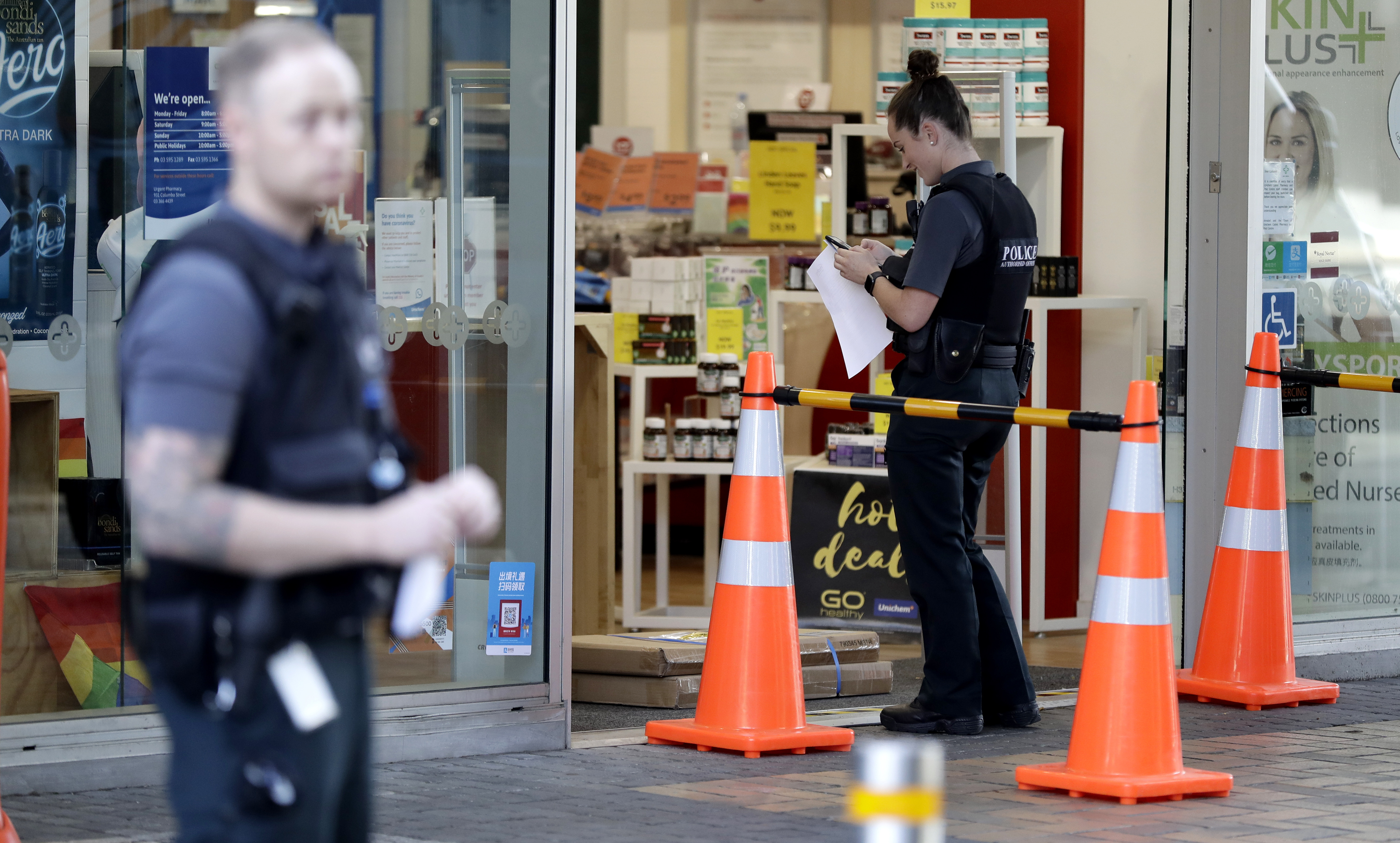 Police queue outside a pharmacy for their influenza injection in Christchurch, New Zealand, Thursday, March 26, 2020.