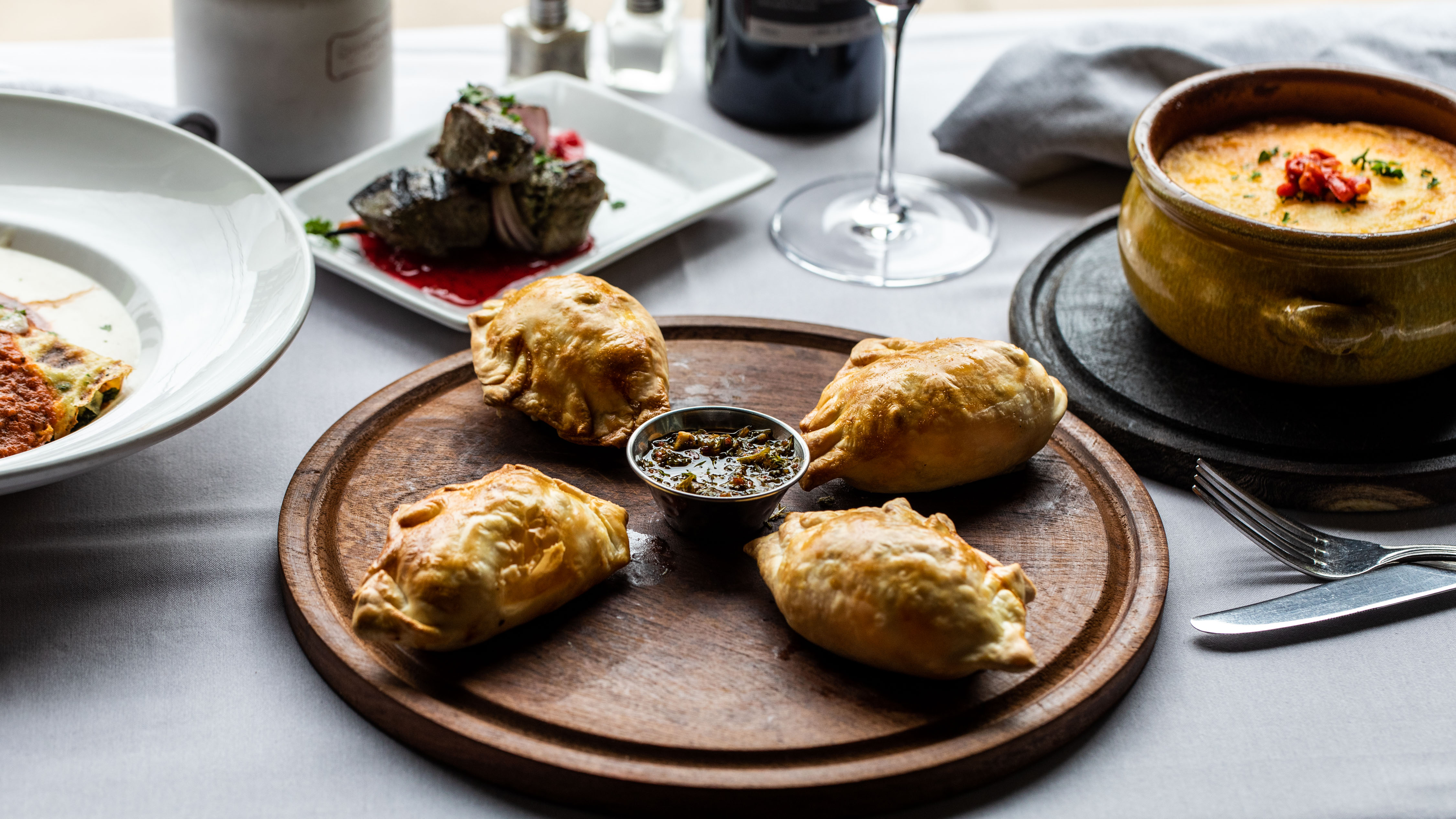 Wooden plate of four empanadas with dipping sauce and other dishes in the background