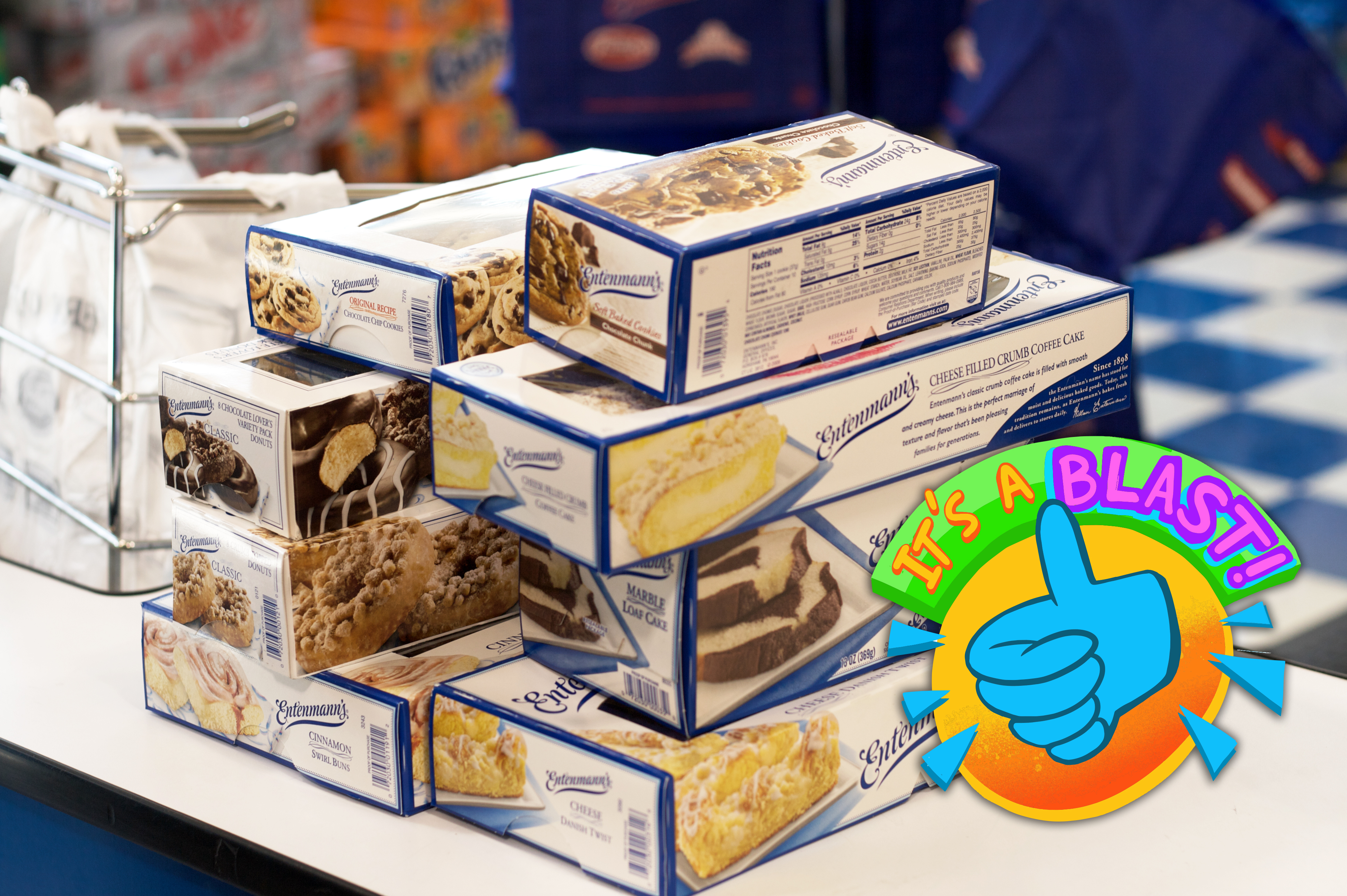 Eight boxes containing different Entenmann's baked items stacked on a checkout counter.