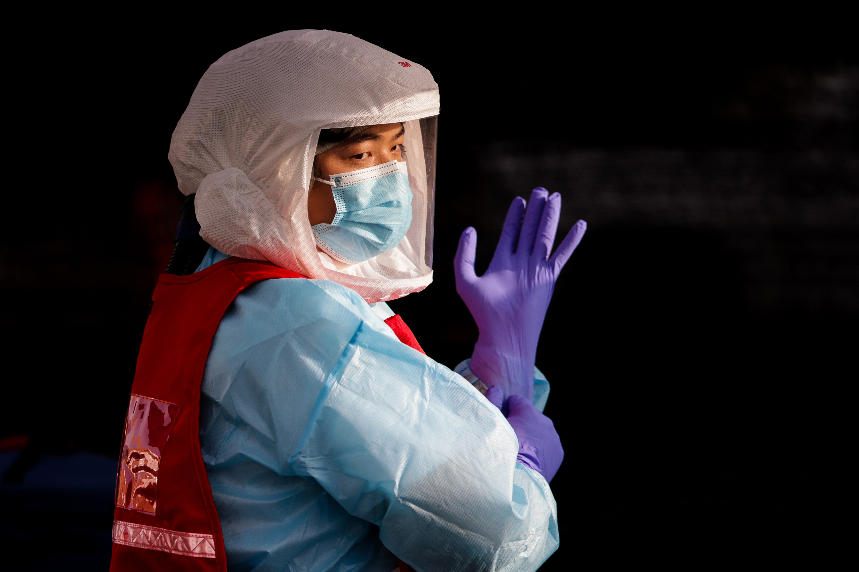Yihao Qin dons new gloves while working at a COVID-19 test site run by the Salt Lake County Health Department at Glendale Middle School in Salt Lake City on Tuesday, Sept. 15, 2020.
