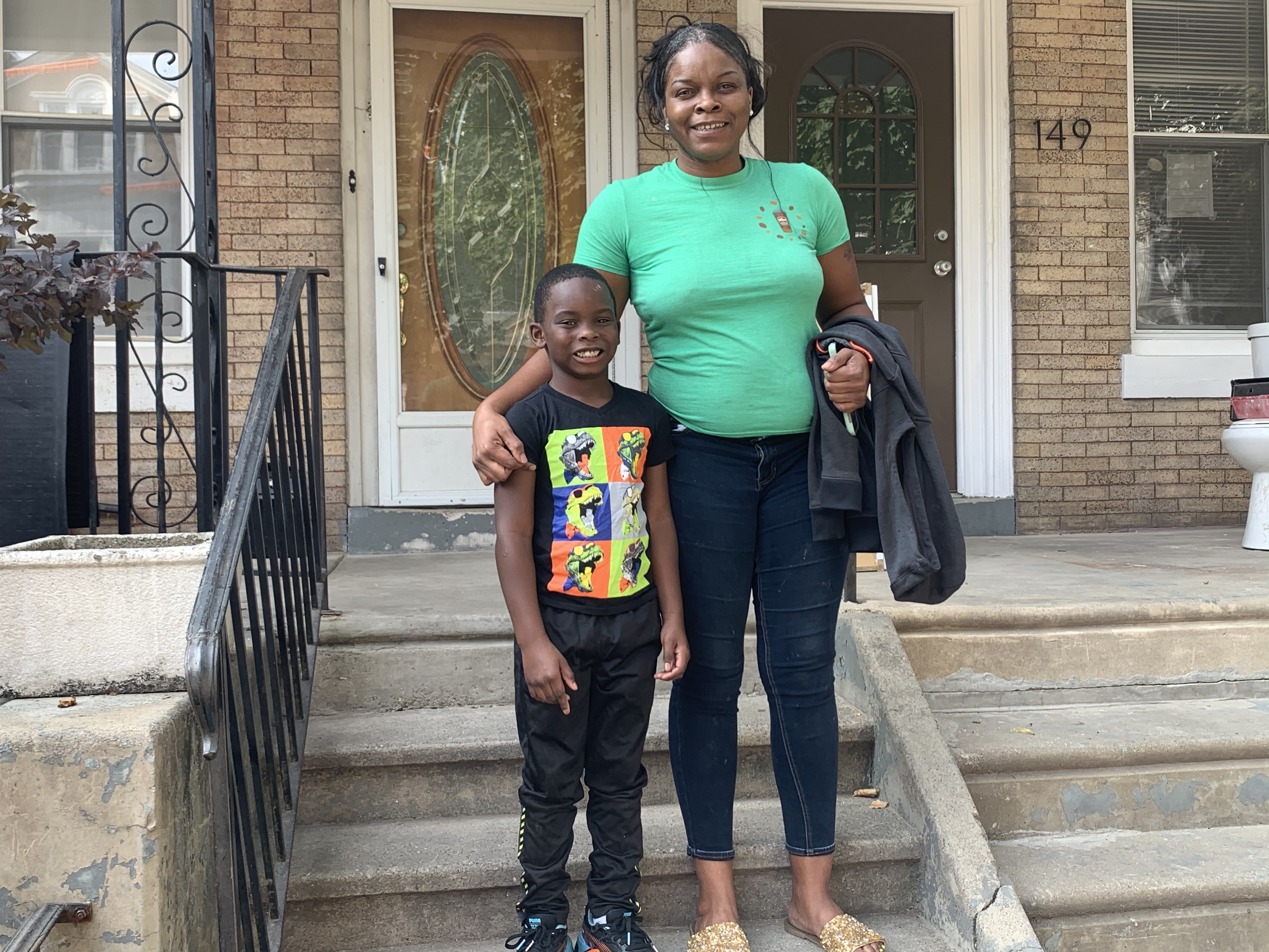 Ashley Chalmers and son Zion in front of their home.