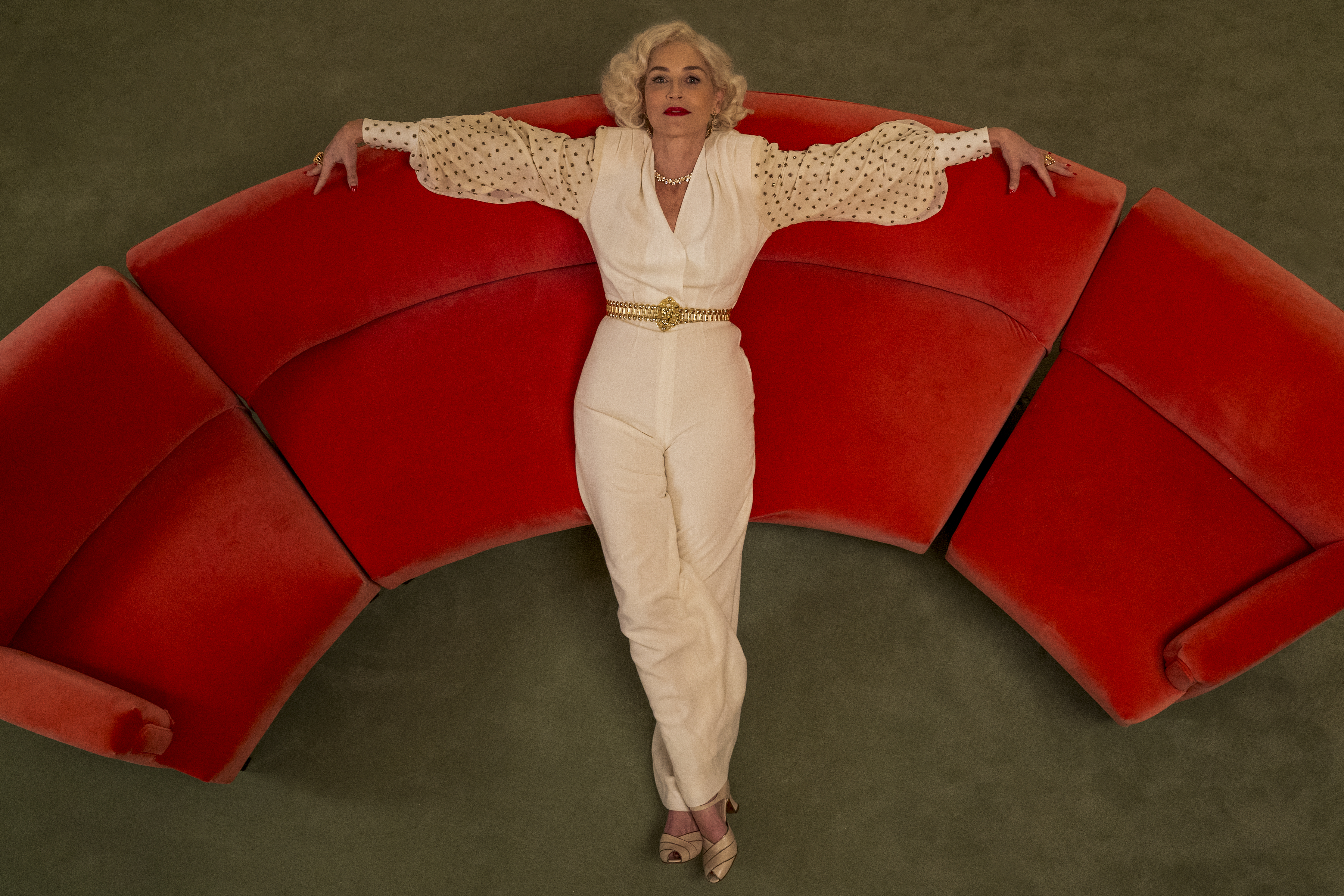 Sharon Stone, dressed in white, lounges on a semi-circular red couch