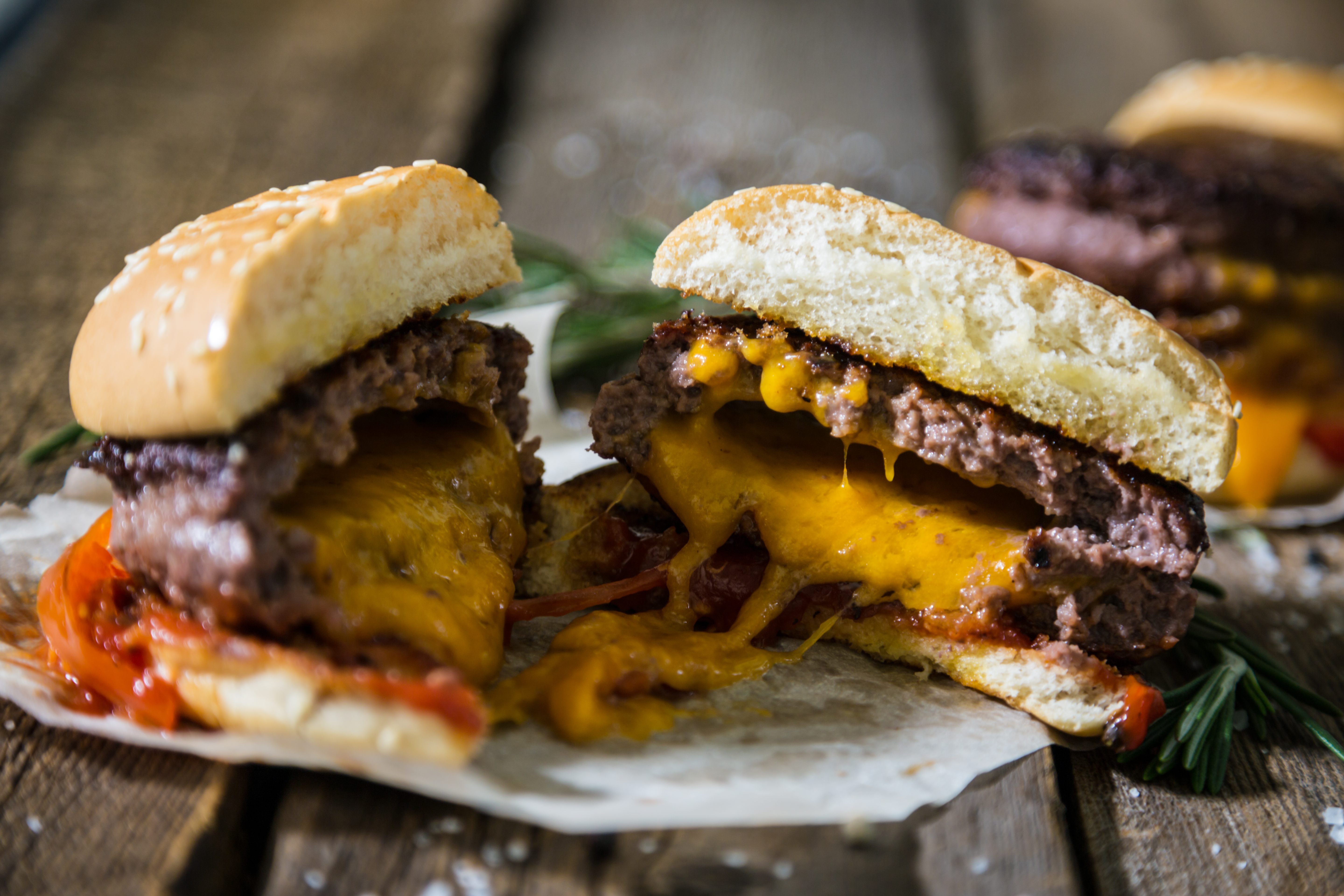 A juicy lucy burger cut in half with cheddar cheese baked into the meat