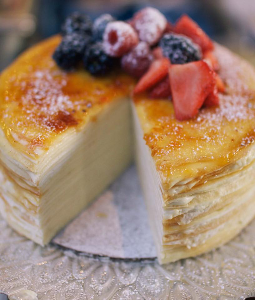 A multilayered crepe cake with a bruleéd top and a pile of berries dusted in powdered sugar. One slice is taken out, giving a view of all the layers mixed with pastry cream.