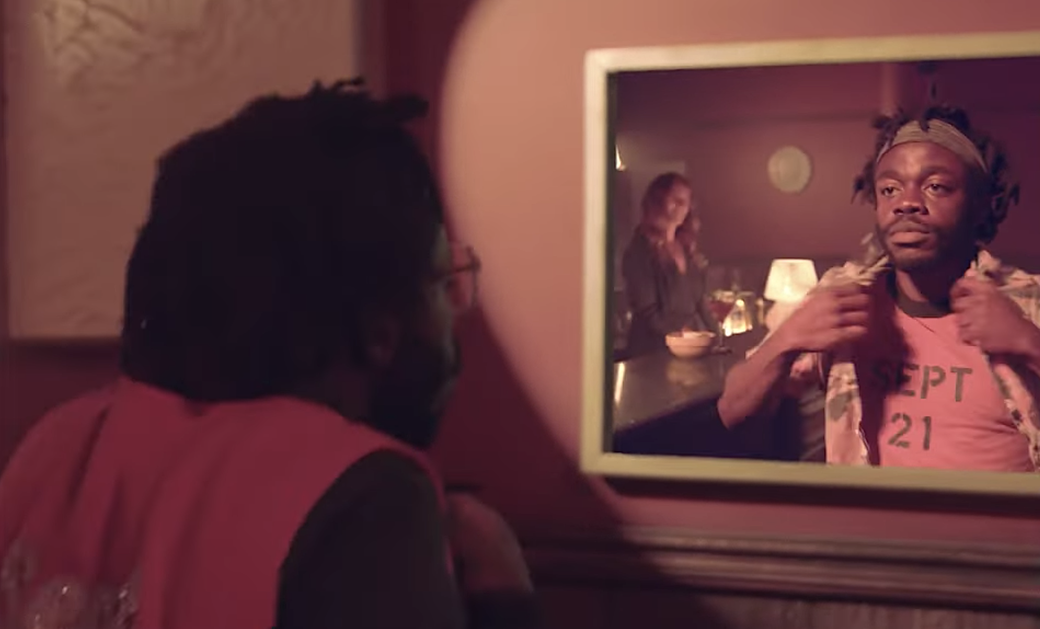 """Demi Adejuyigbe looks in a mirror in his 9/21/21 video celebrating Earth, Wind & Fire's """"September"""""""