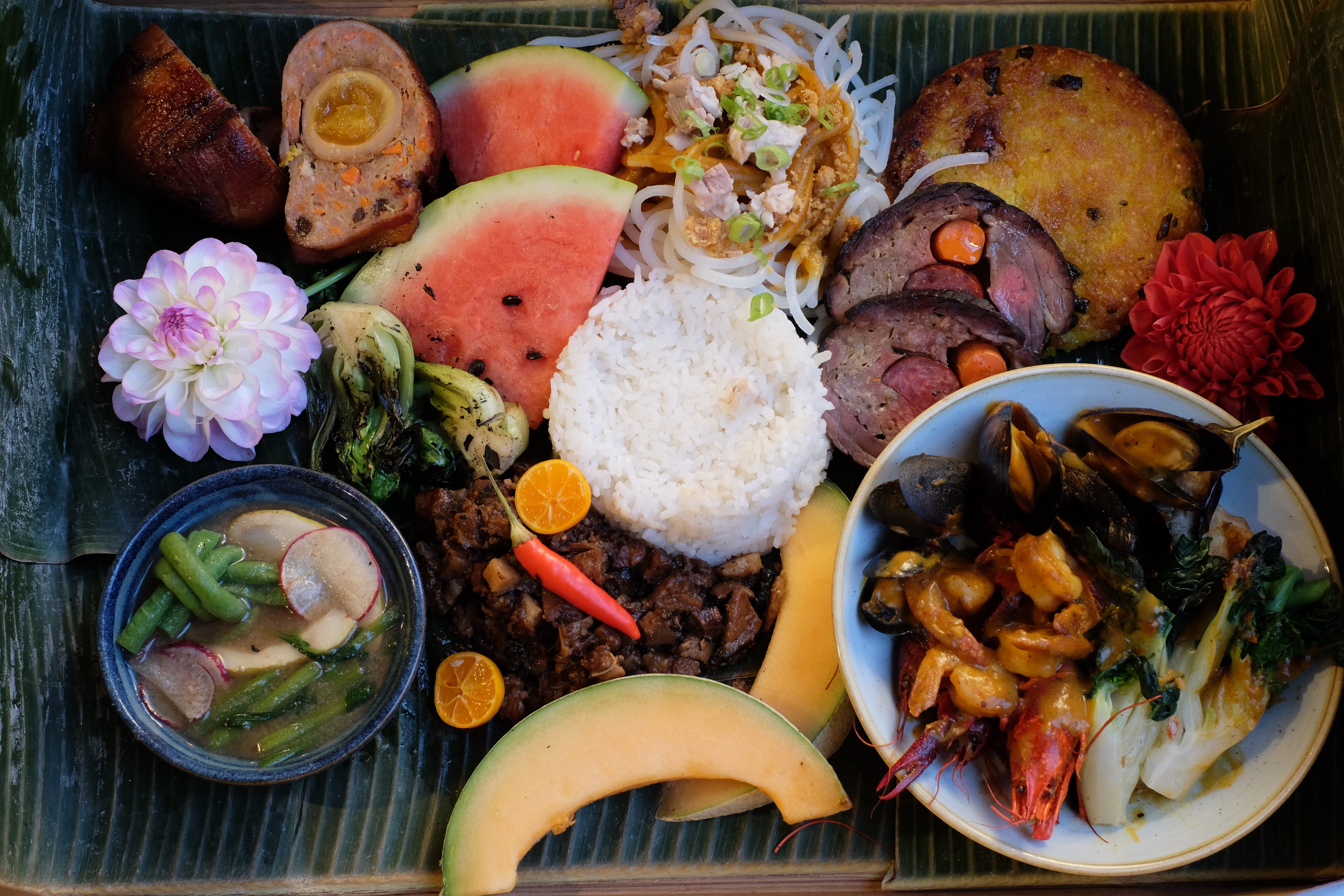 A spread of dishes laid out on banana leaves, including pork sisig, crispy sticky rice, and slices of fresh melon