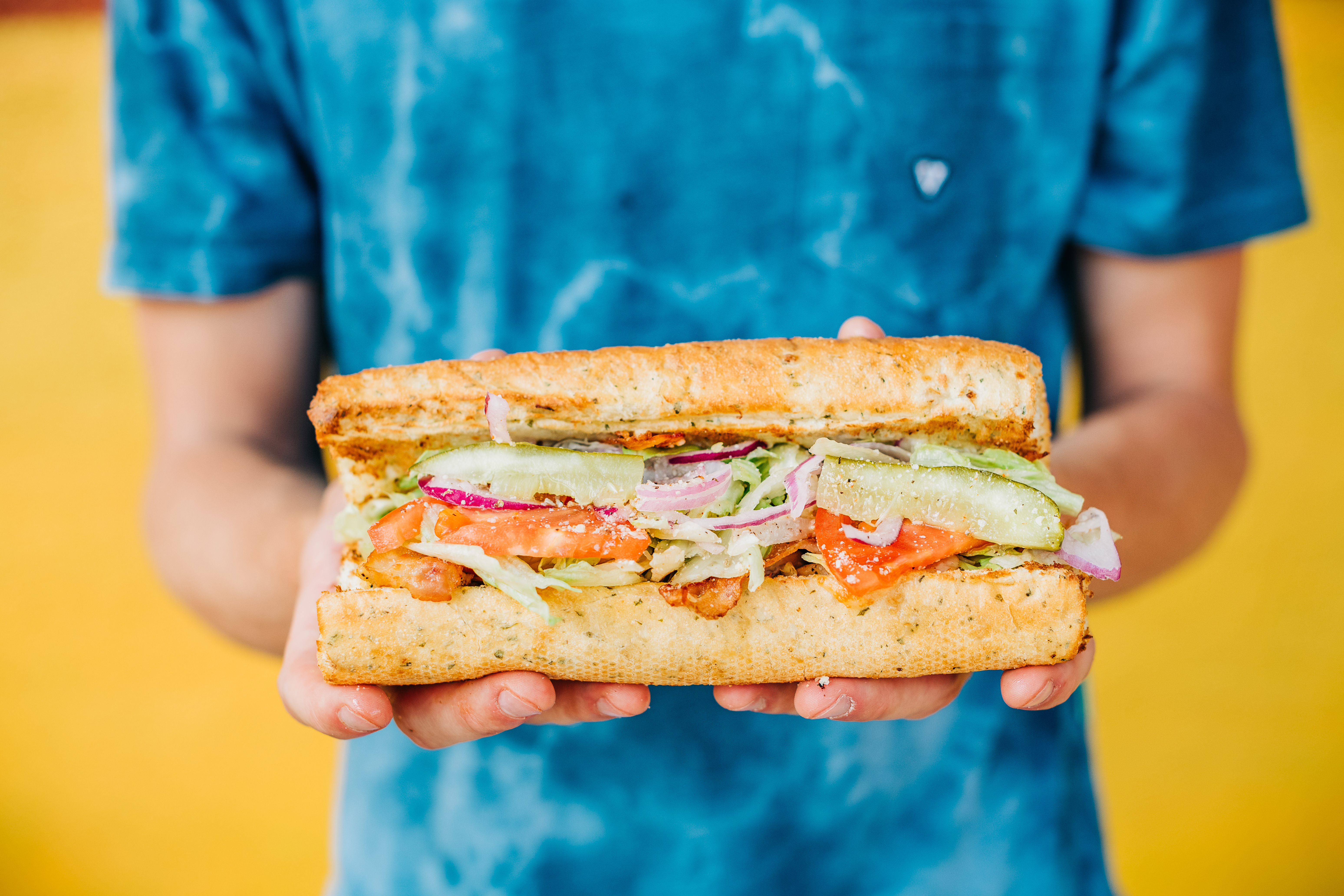 A person in a tie-dyed blue tee shirt standing in front of bright yellow wall holds a 12-inch sub sandwich stuffed with meats, pickles, tomatoes, and lettuce