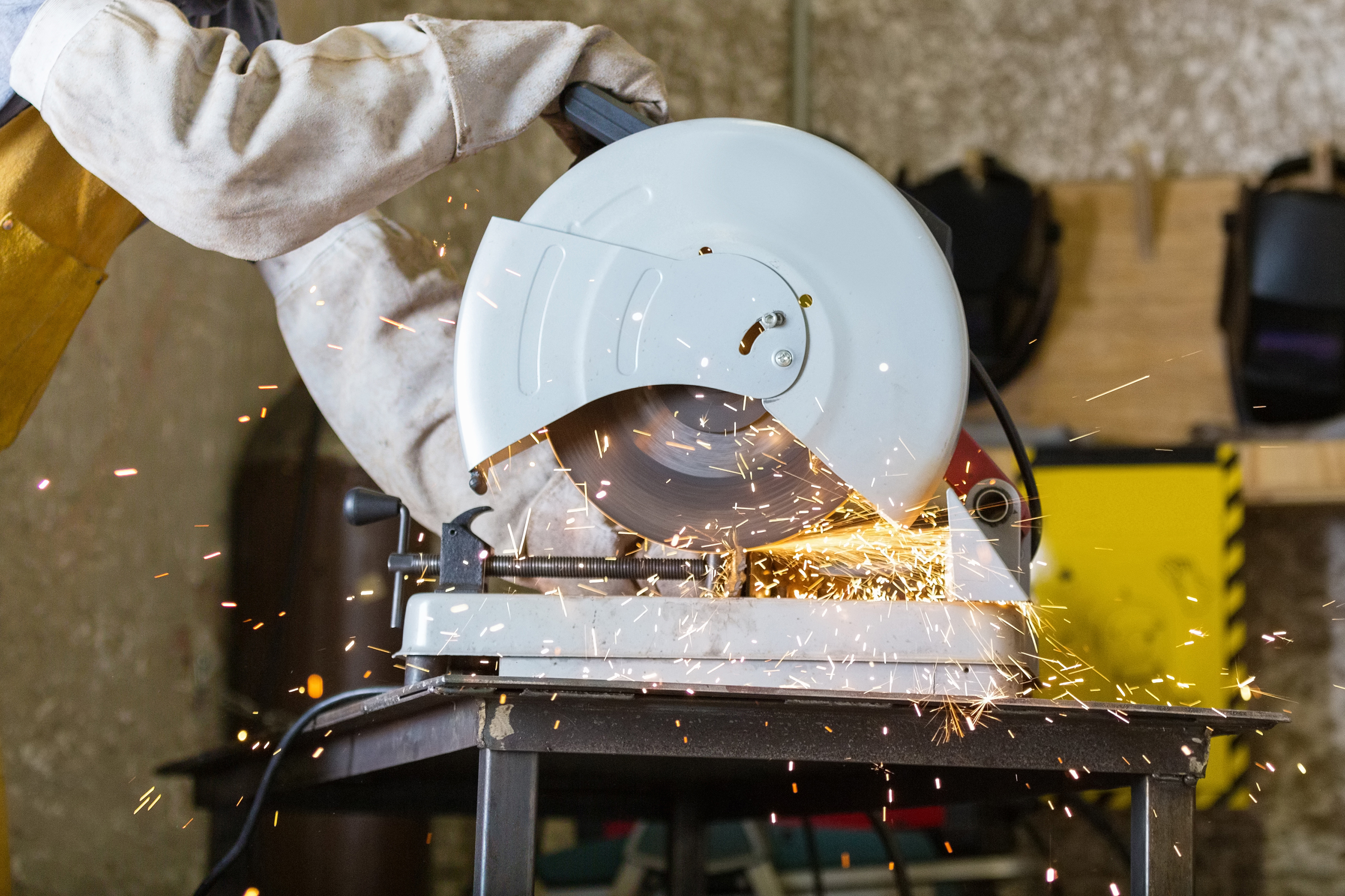 Man wearing protective clothing while using a table saw to cut metal.