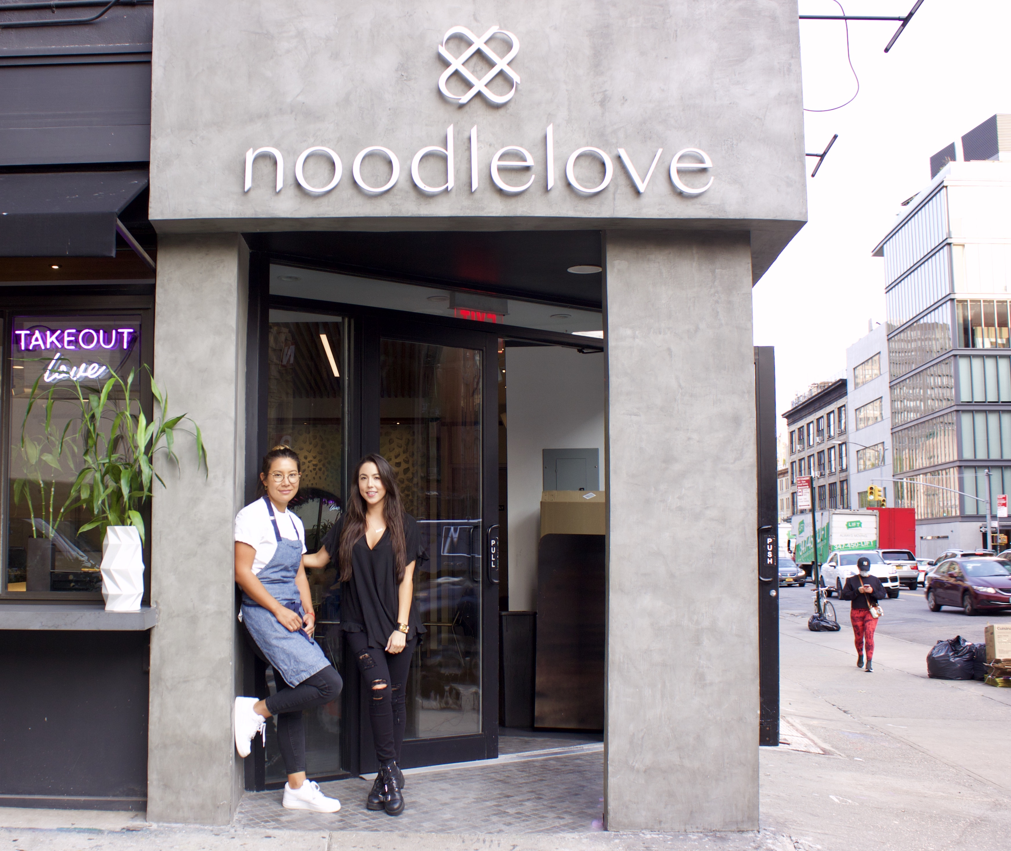 Two women standing in front of a restaurant with a gray exterior
