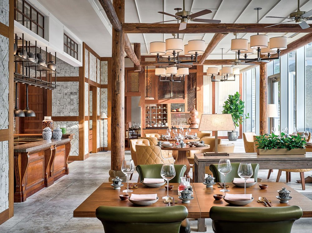 A restaurant interior with wood beams, cement floors, and green and cream colored chairs