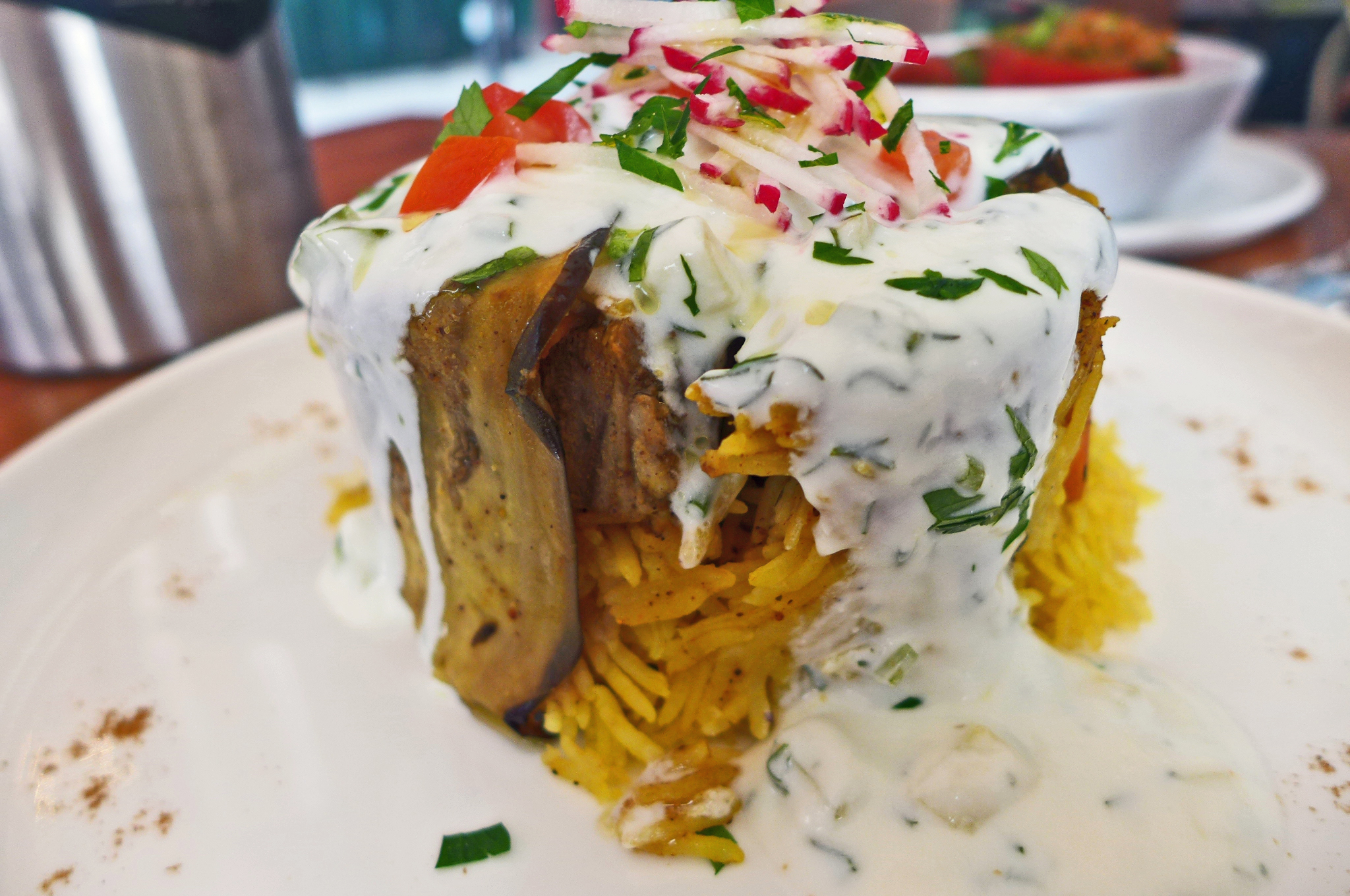 A vast mass of yellowish rice in a cone with white sauce flowing over the top.
