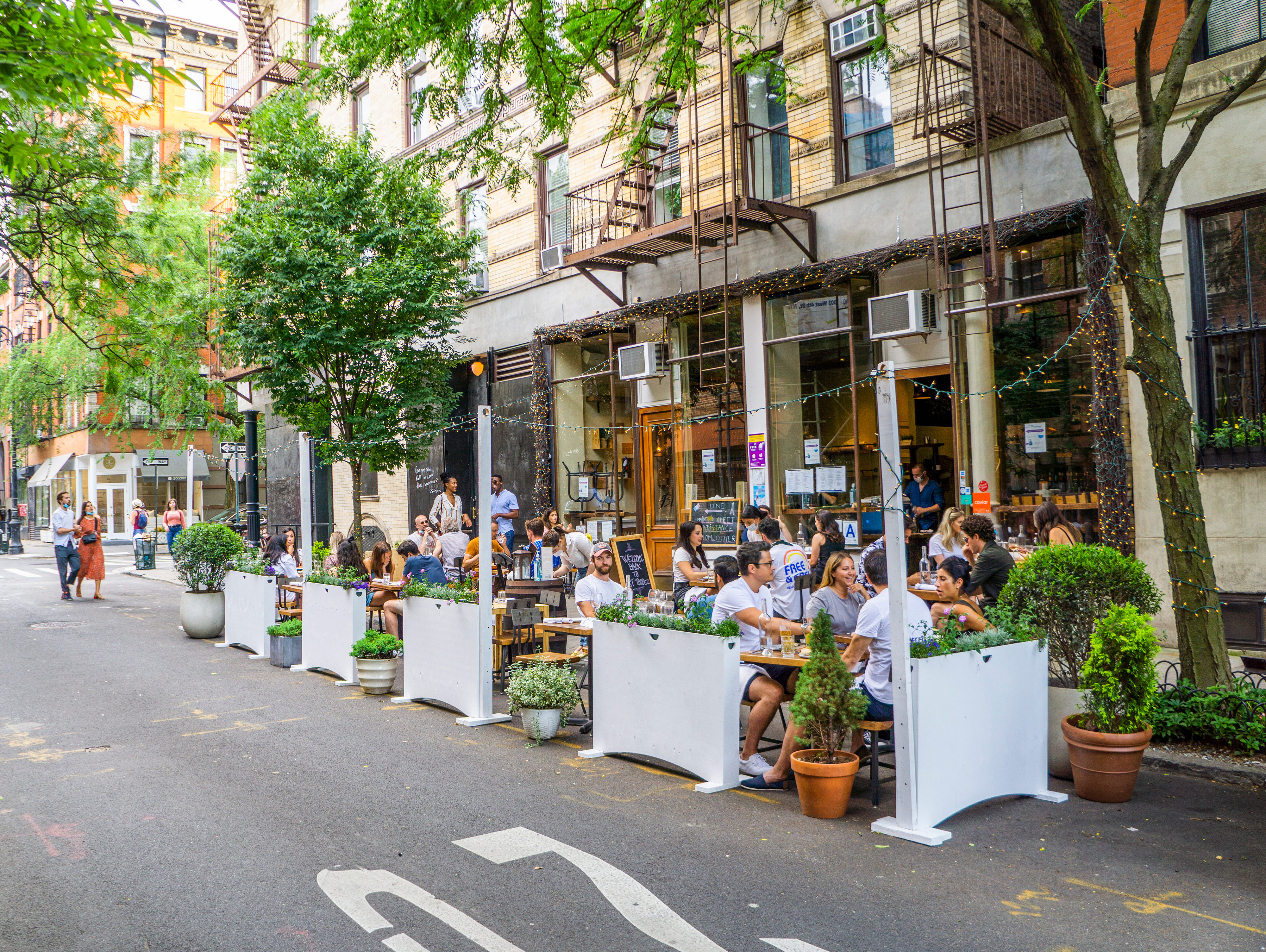 """An exterior view of outdoor street dining on a New York City street. The photo is for an article on the Department of Justice's designation of NYC as an """"anarchist jurisdiction."""""""