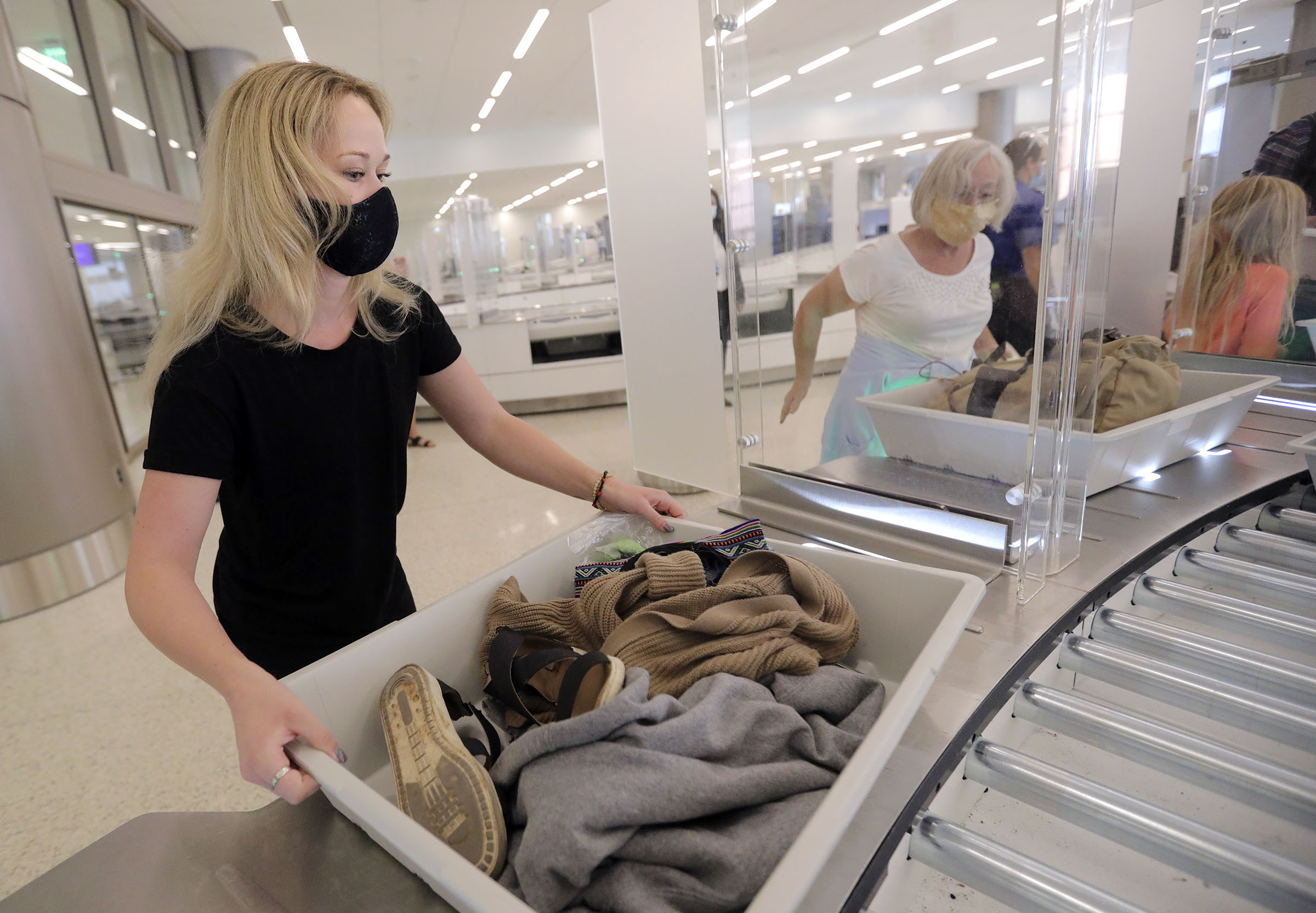 Reagan Peterson puts her belongings in a bin for screening at the Transportation Security Administration checkpoint at the new Salt Lake City International Airport in Tuesday, Sept. 22, 2020. The bins are 25% larger than normal bins.