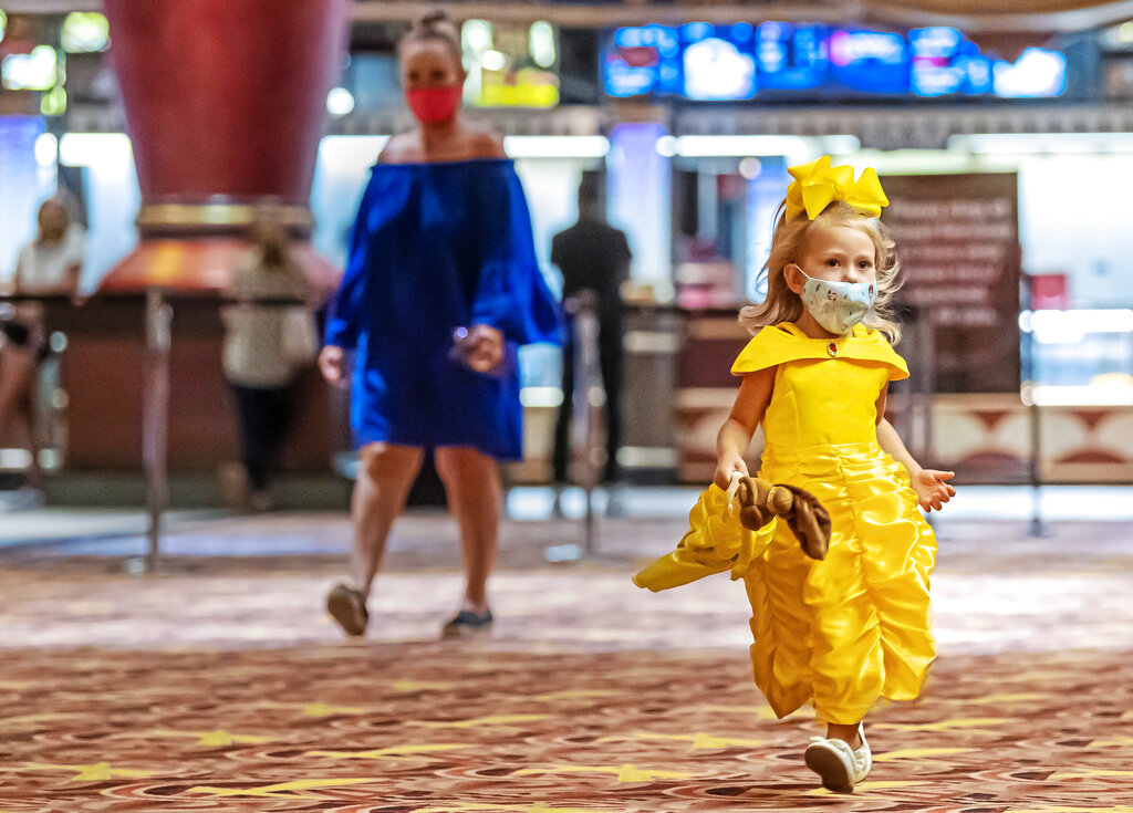 """Dressed as Disney's Belle, Lilly Stevenson, 3, of McMurray, Pa., holds her Belle doll as she makes her way to see """"Beauty and the Beast,"""" during AMC Waterfront movie theater's reopening on Thursday, Aug. 20, 2020, in West Homestead, Pa. (Steph Chambers/Pittsburgh Post-Gazette via AP)"""