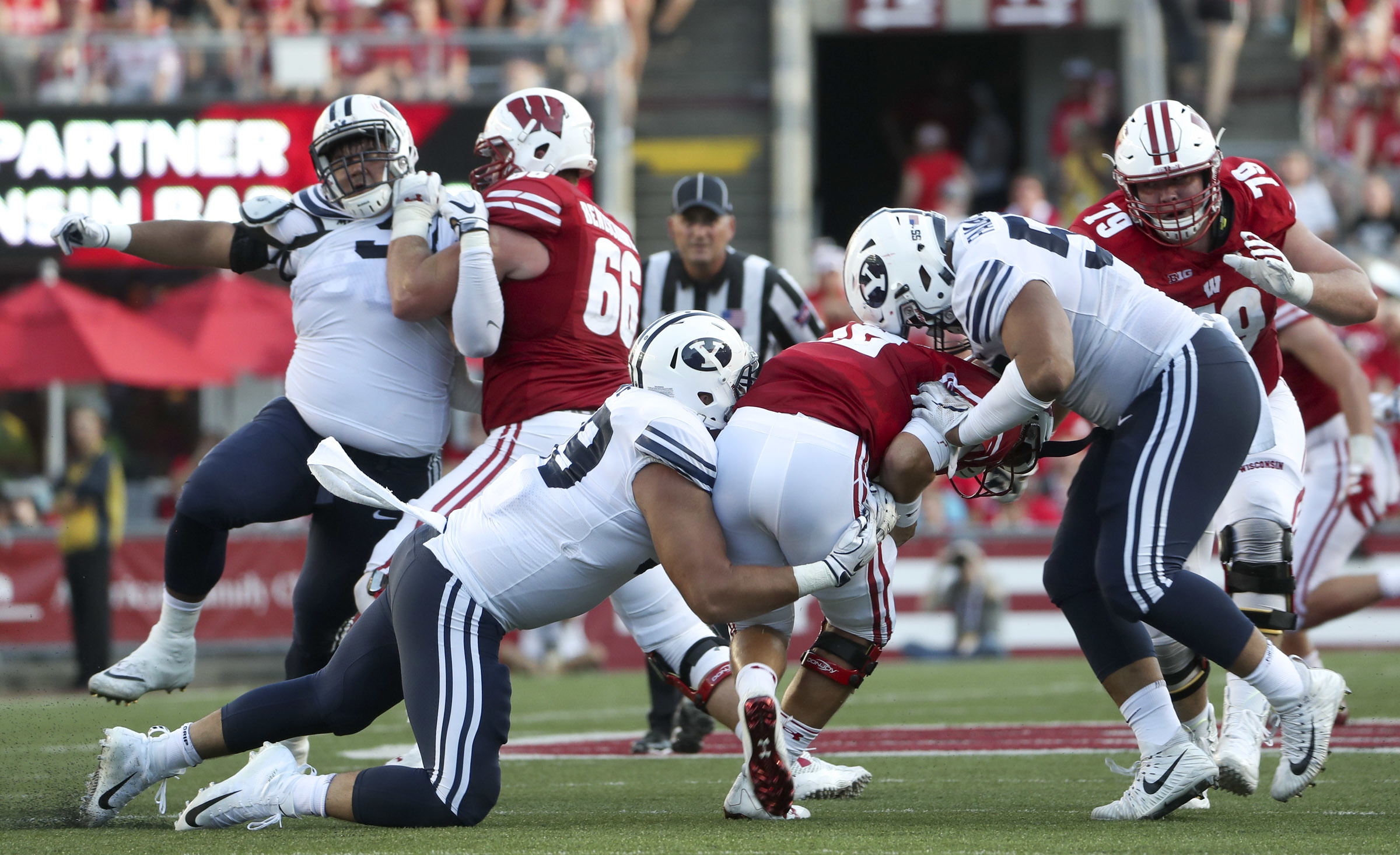 Brigham Young Cougars defensive linemen Lorenzo Fauatea (55) and Zac Dawe (99) sack Wisconsin Badgers quarterback Alex Hornibrook (12) during the Wisconsin-BYU football game at Camp Randall Stadium in Madison, Wisconsin, on Saturday, Sept. 15, 2018. Fauatea is among BYU players asking officials to let family members attend Saturday's game vs. Troy in Provo, which was moved to the moderate risk level designation for COVID-19 on Tuesday, Sept. 22, 2020.