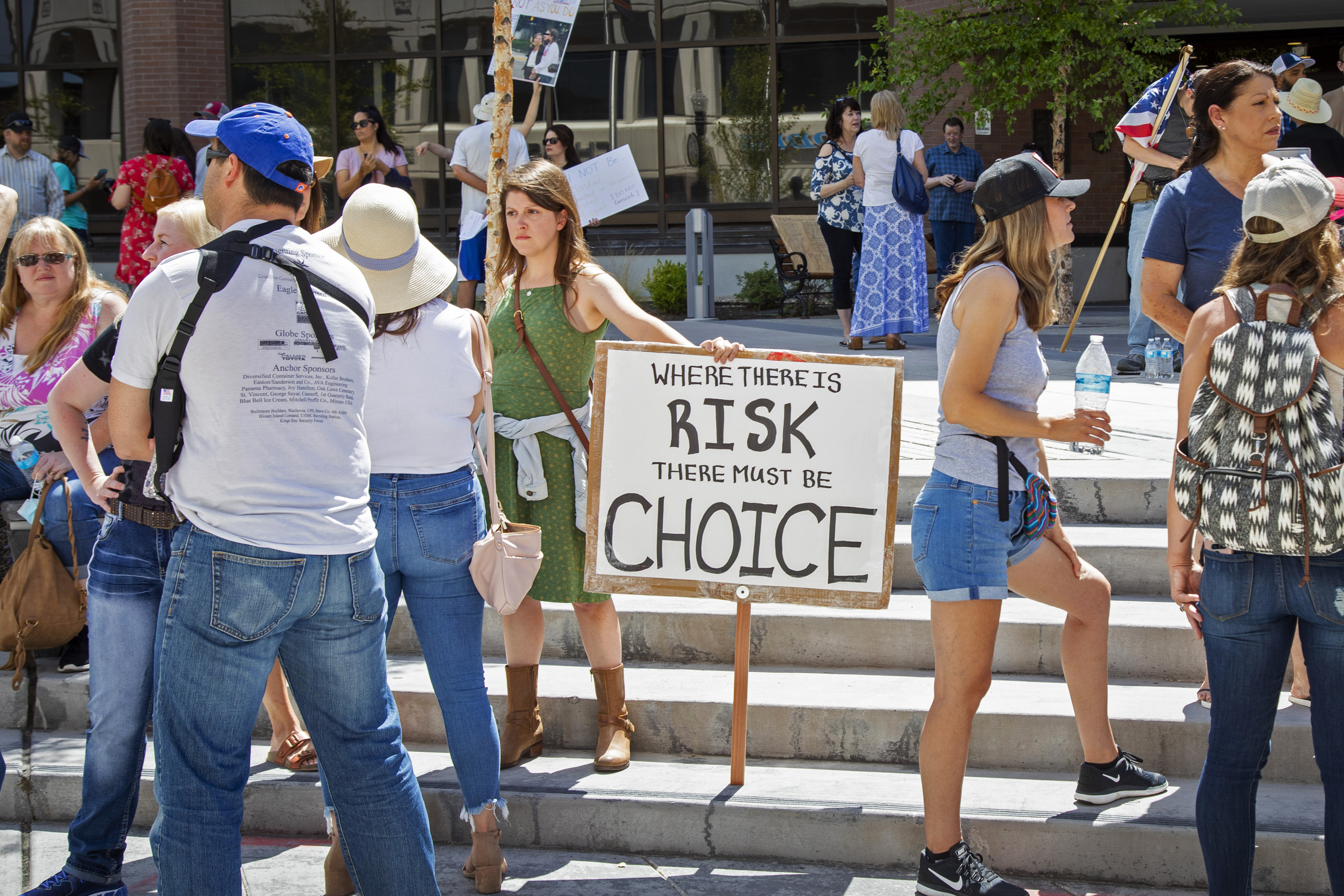Emily Wahl, center, and more than 100 other people gather at City Hall to protest Mayor Lauren McLean's order mandating people to wear face coverings in Boise, Idaho, Friday, July 3, 2020.