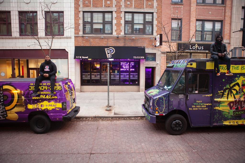 Two African-American men sit on top of a van and food truck in front of a storefront restaurant.