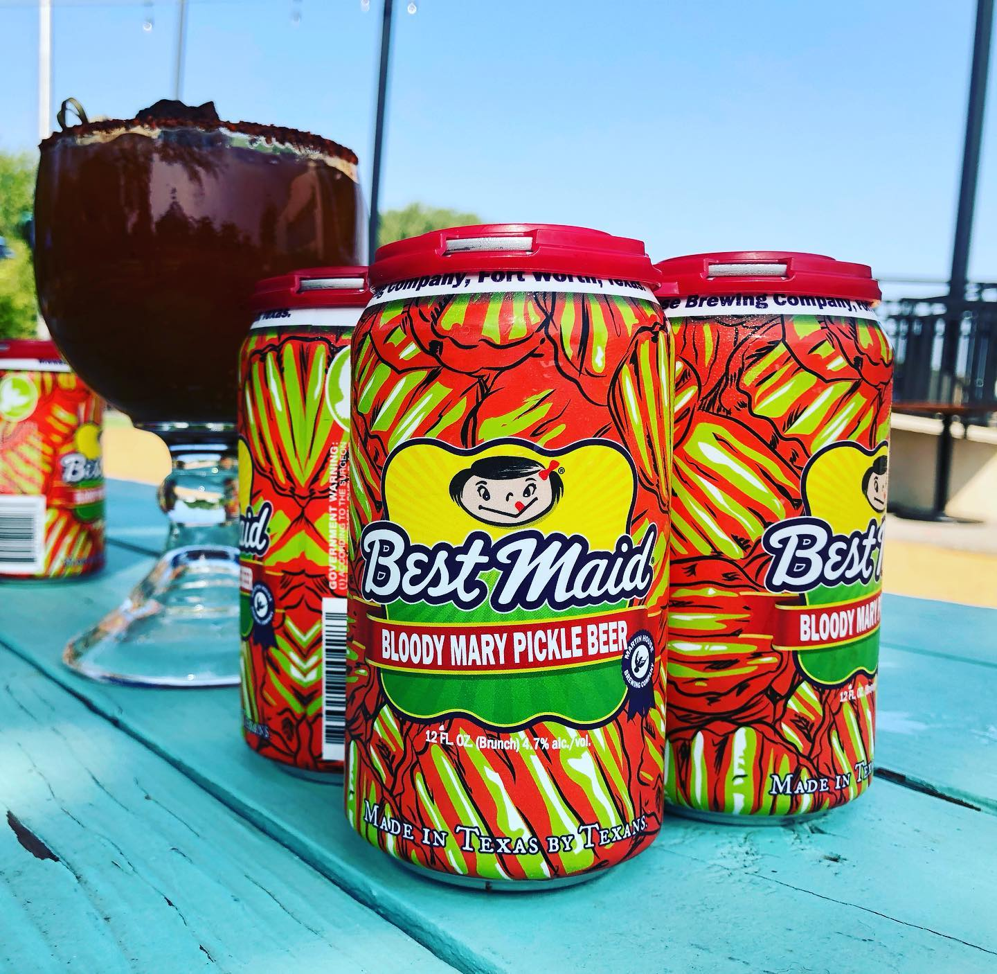 "a four-pack of beers, the cans of which are bright green and red. The name of the beer is ""bloody mary pickle beer."" They are sitting on a blue-painted picnic table and in the background there is a large mug filled with a dark red liquid."