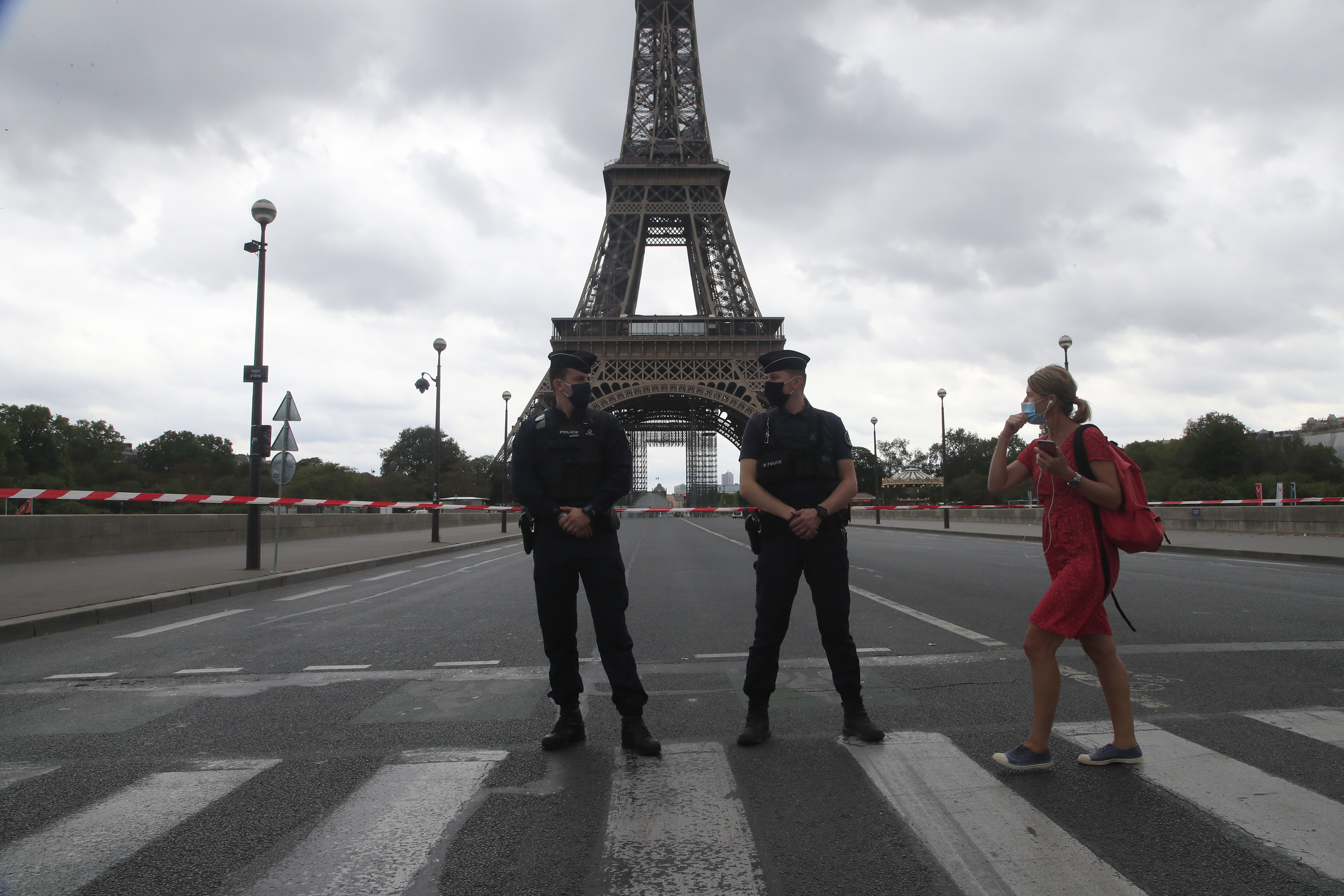 A woman walks past police officers securing the bridge leading to the Eiffel Tower, Wednesday, Sept. 23, 2020 in Paris. Paris police have blockaded the area around the Eiffel Tower after a phone-in bomb threat.