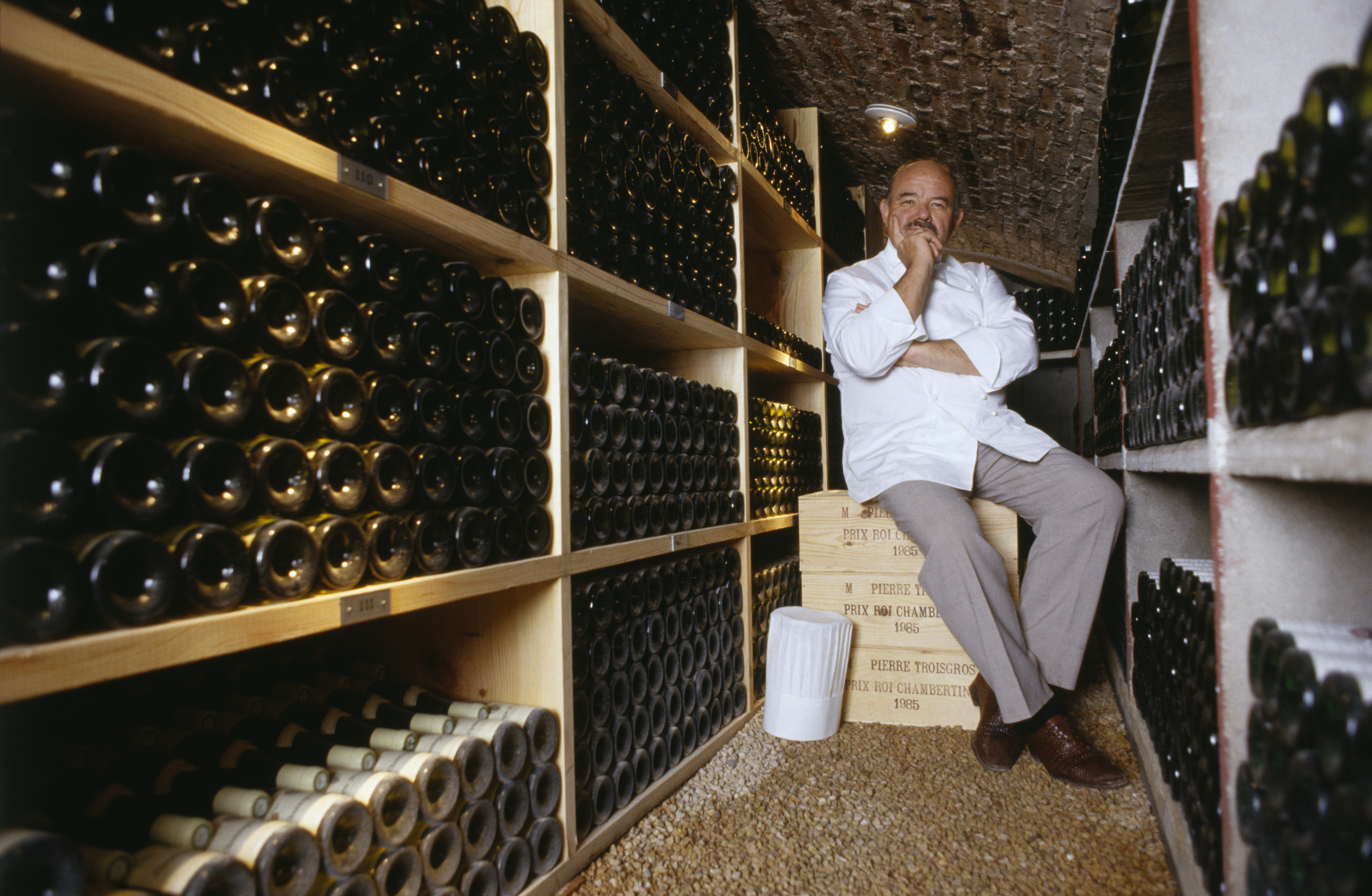 Man sitting on a crate inside a wine cellar.