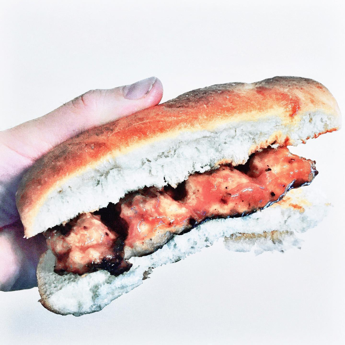 A hand holds a McRib-style sandwich on a white background