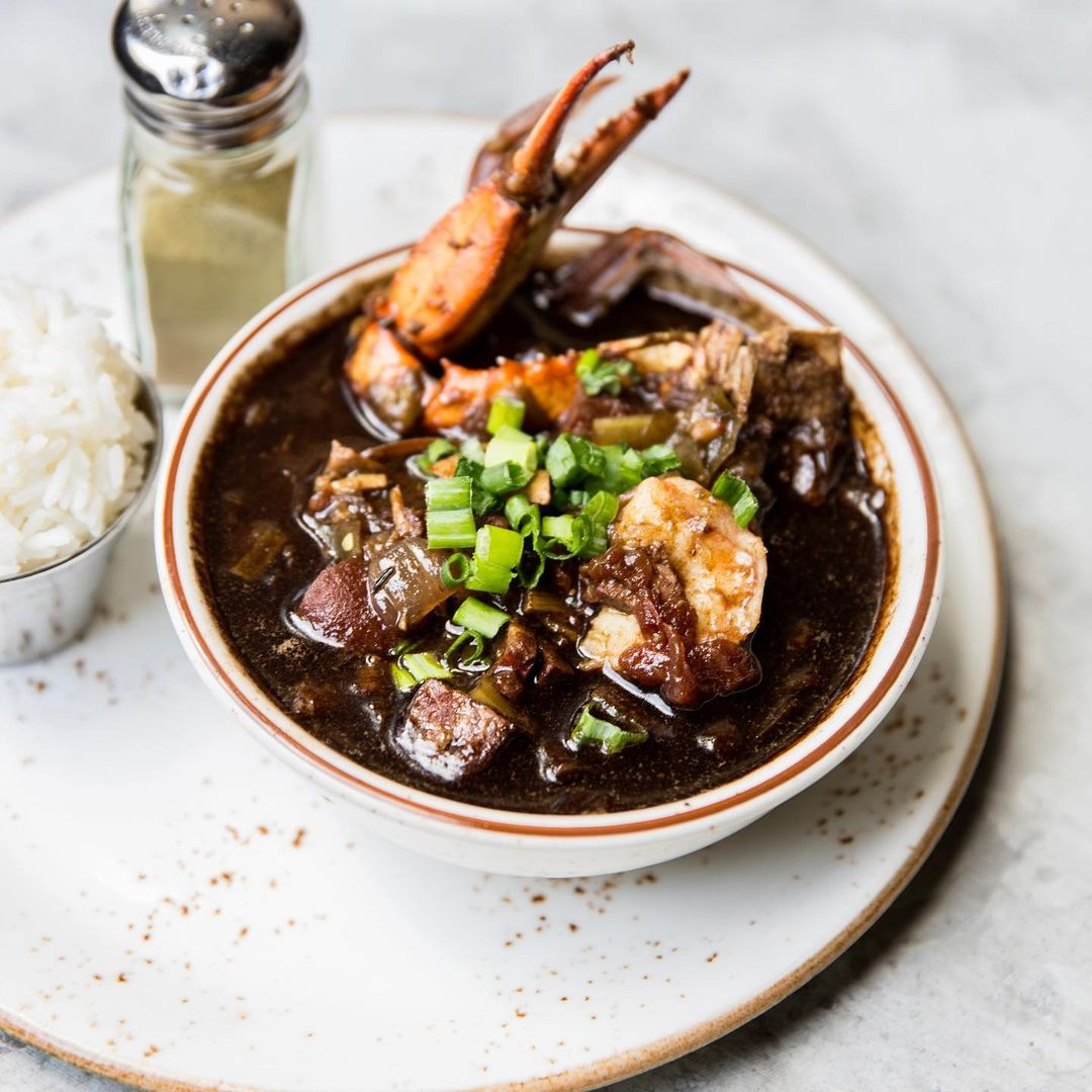 a bowl full of super rich-looking dark brown gumbo with a crab claw sticking out of it, next to a salt shaker, on a white marble plate