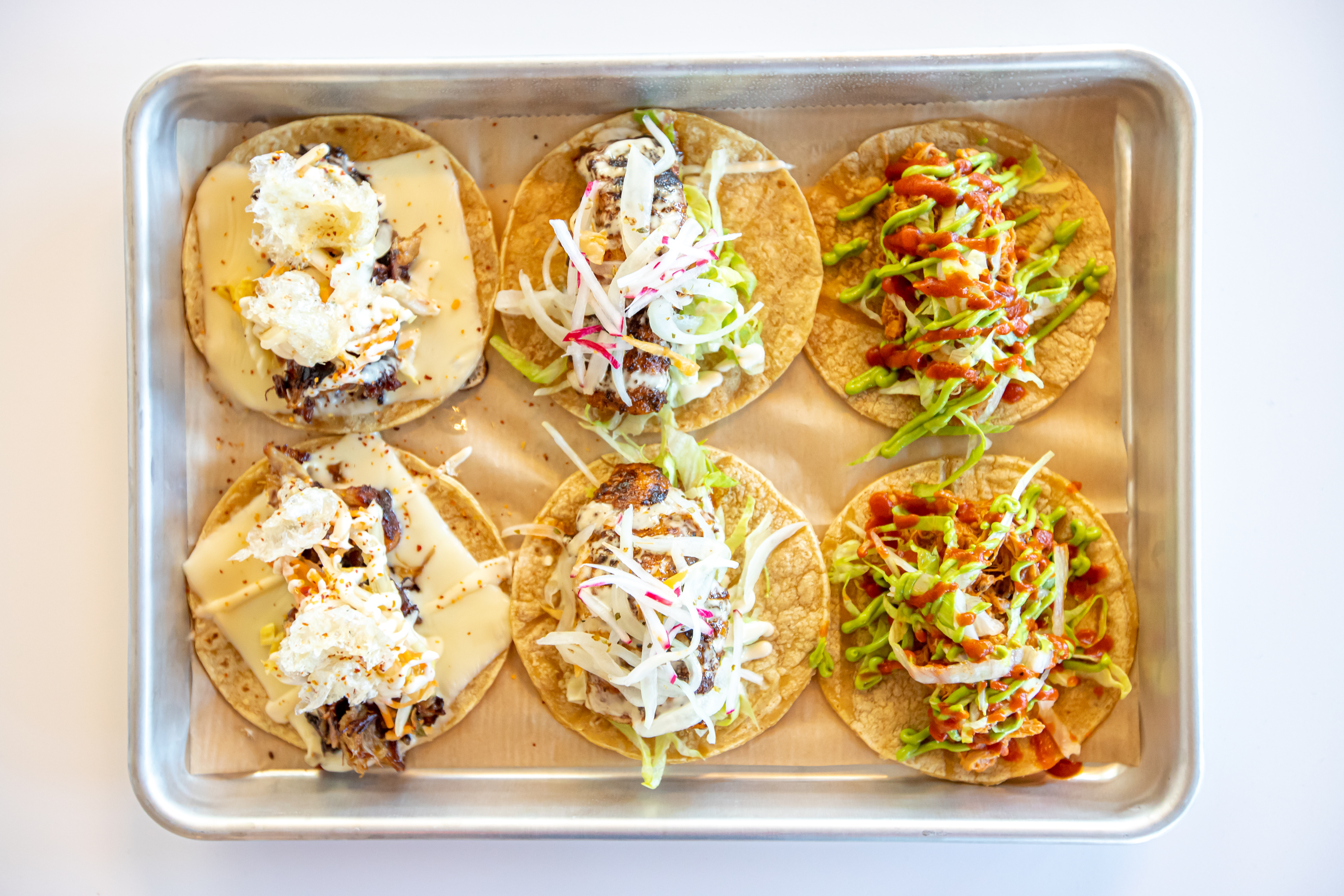 Tacos stuffed with orange soda braised carnitas, three chile-spiced catfish, and mojo braised chicken from Hi/Fi Taco
