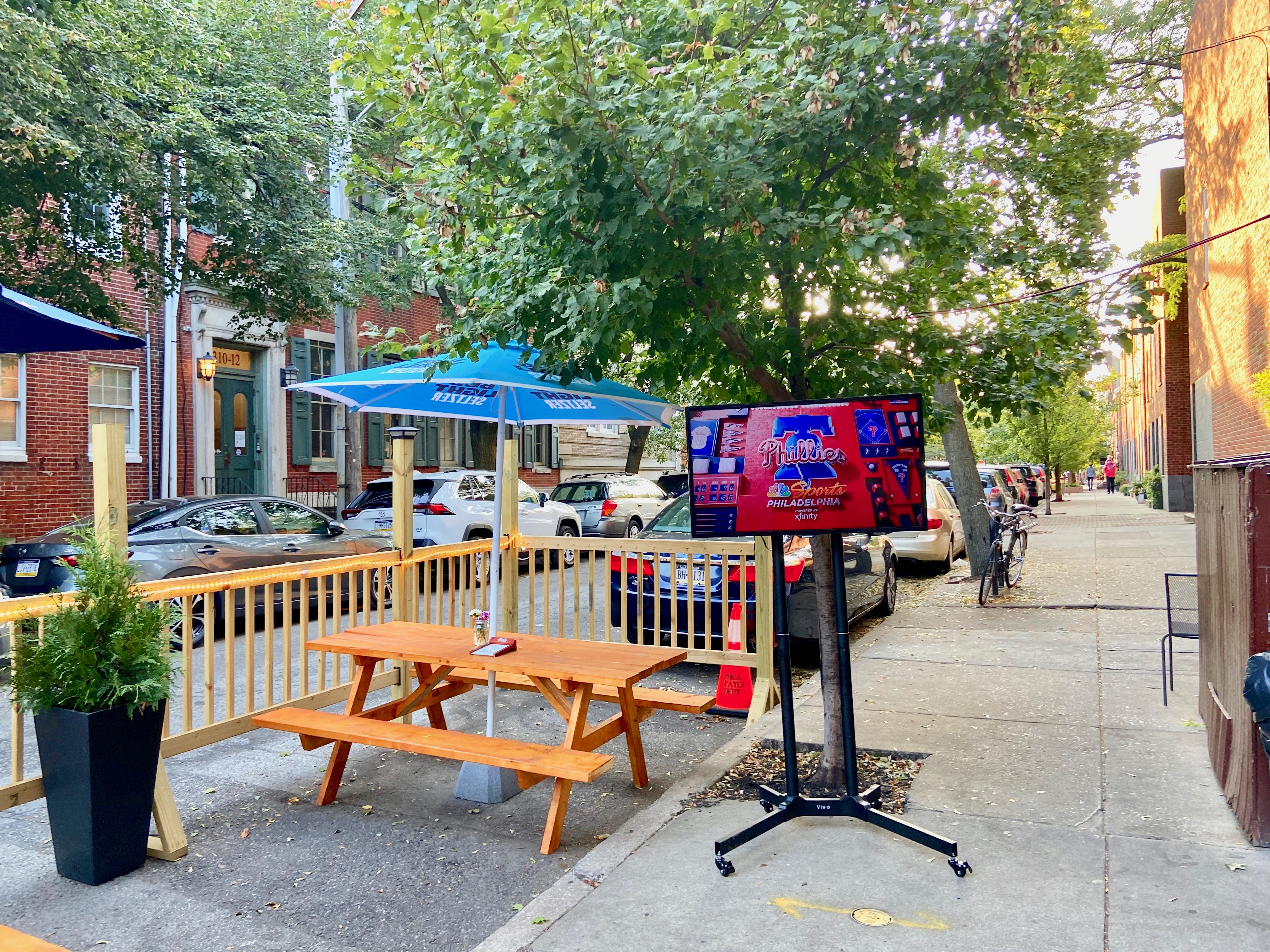 picnic table with umbrella next to a TV on a city street with trees