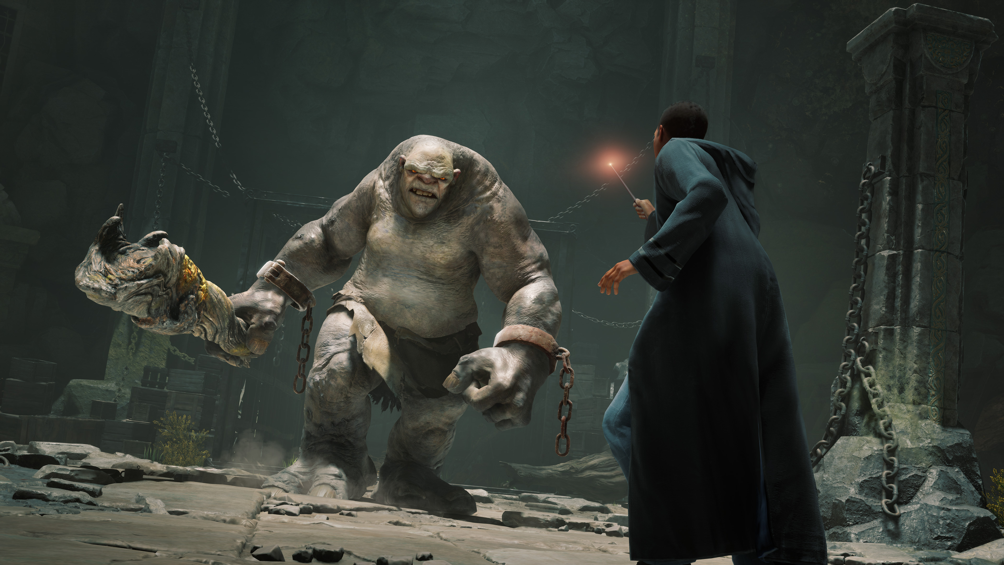 a Hogwarts student brandishes his wand as a troll advances toward him in Hogwarts Legacy