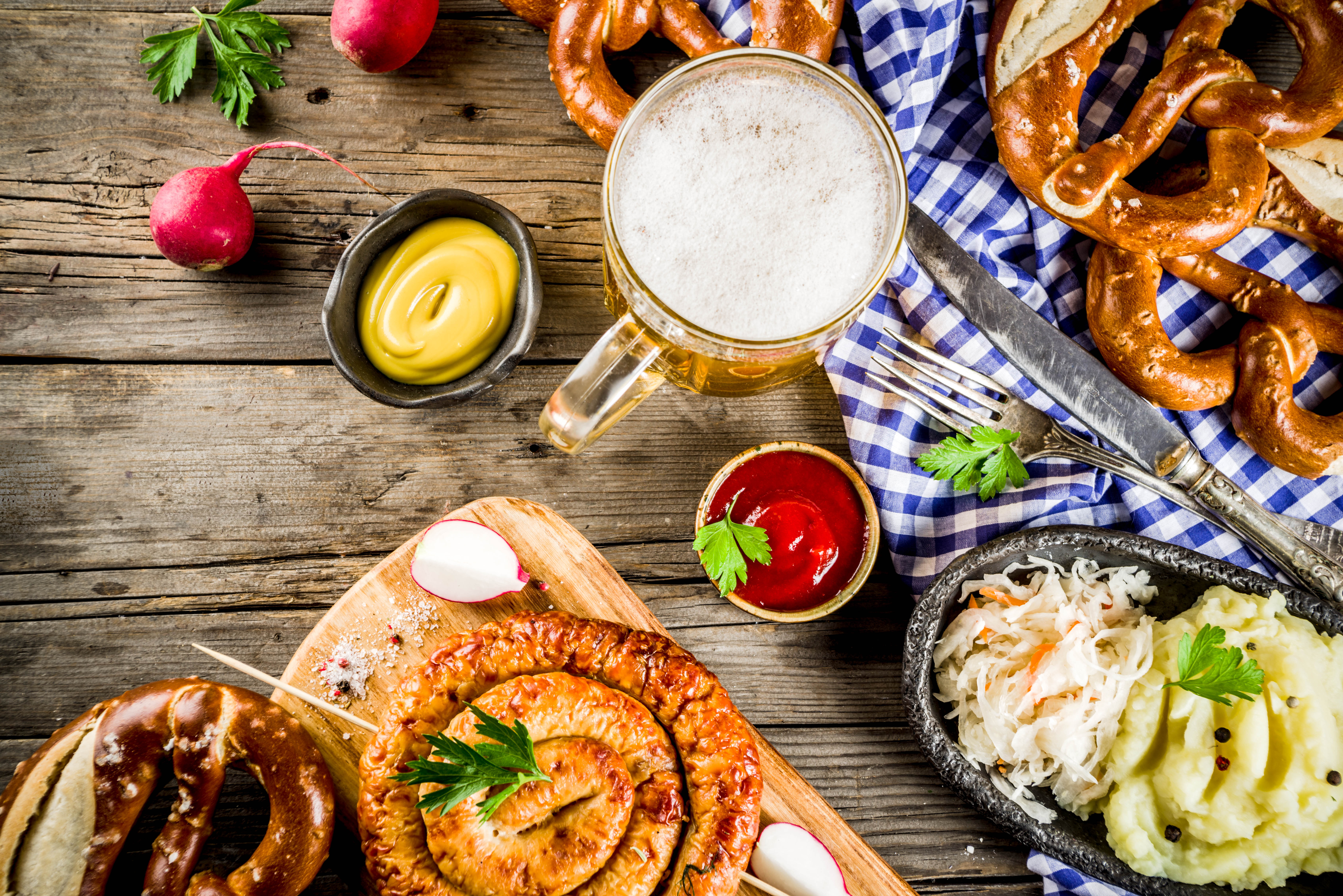 A top-down view of a food and drinks spread, with pretzels, a stein filled with beer, sausages, coleslaw, and potato salad