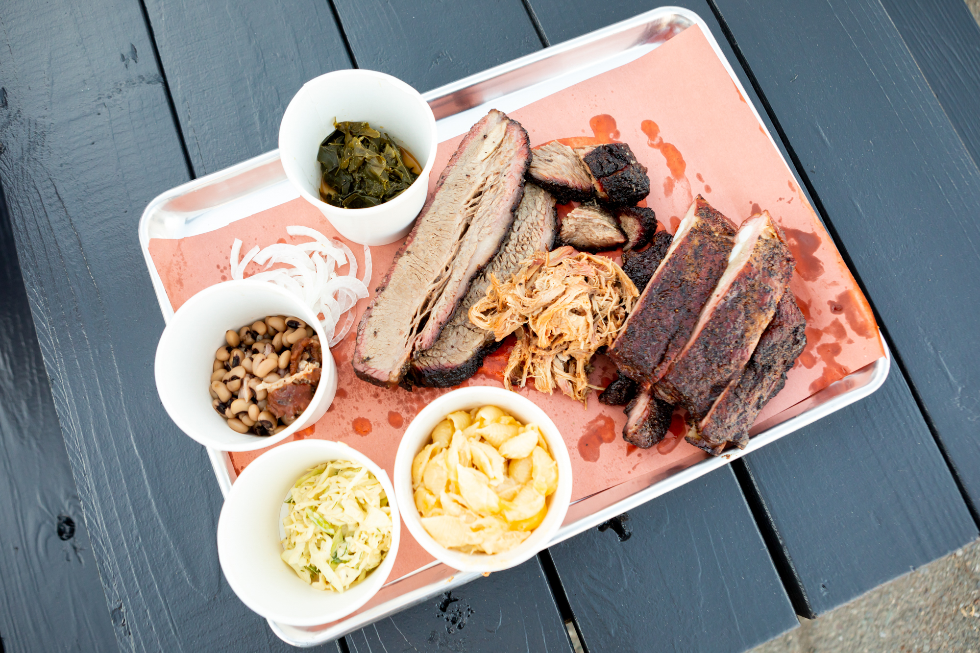 Overhead view of a tray of barbecue —brisket, ribs, pulled pork, and tubs of mac and cheese and cole slaw — on a paper-lined sheet tray