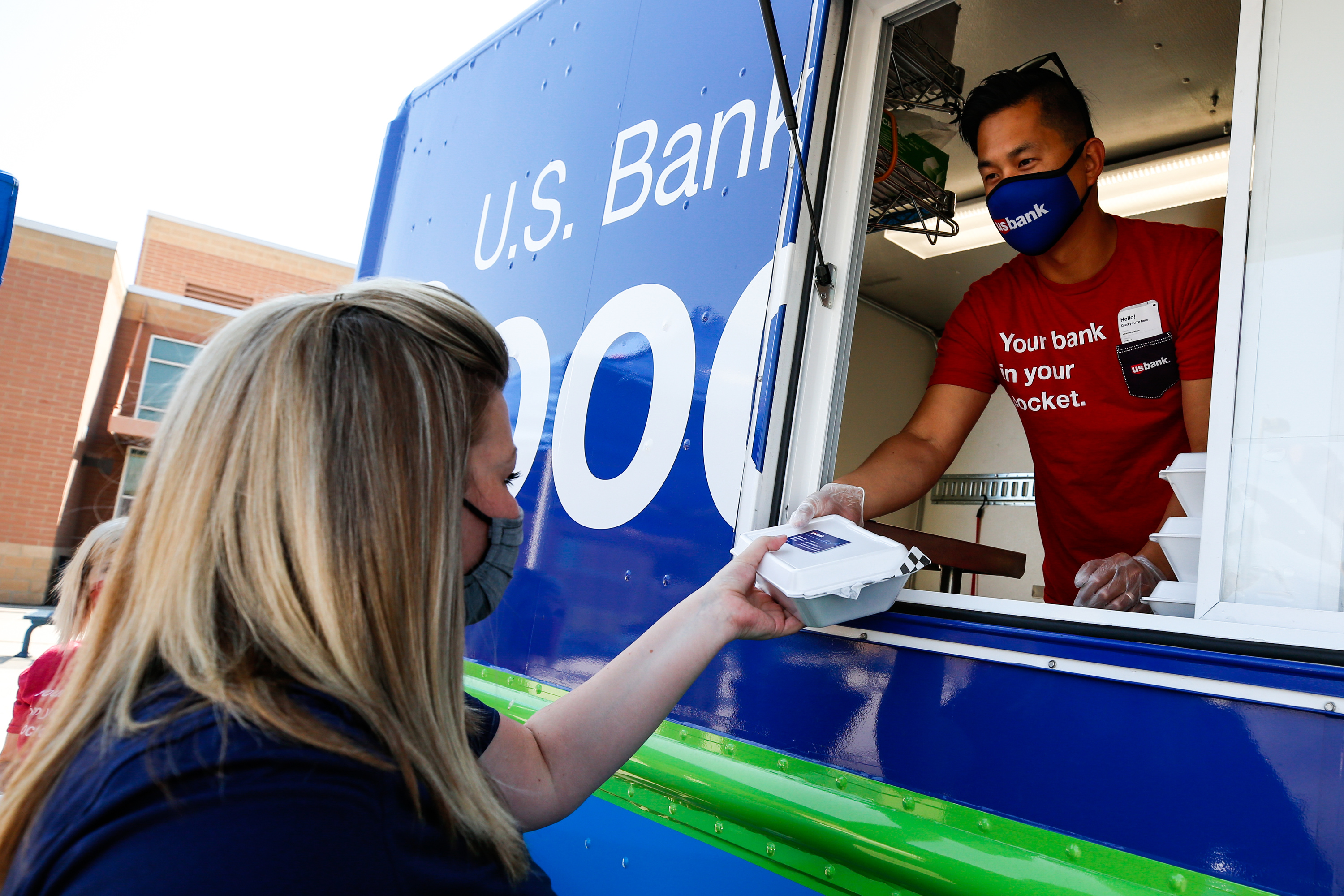 Jimmy Choi hands a boxed lunch to to Tara Spencer, a counselor at Westlake High School in Saratoga Springs, on Thursday, Sept. 24, 2020. U.S. Bank's Good Truck, which is traveling the country to support small businesses and honor frontline employees that are working to keep their communities going during the pandemic, made a stop at the school and treated educators to a free lunch from Kluck's Krispy Chicken.
