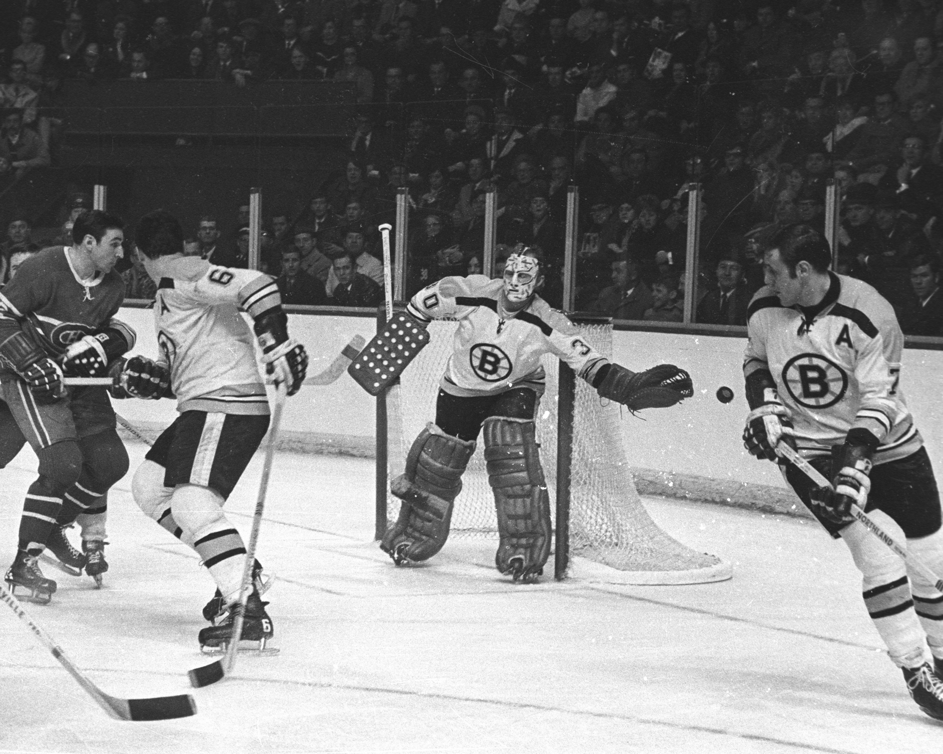 Gerry Cheevers deflects the puck wide...