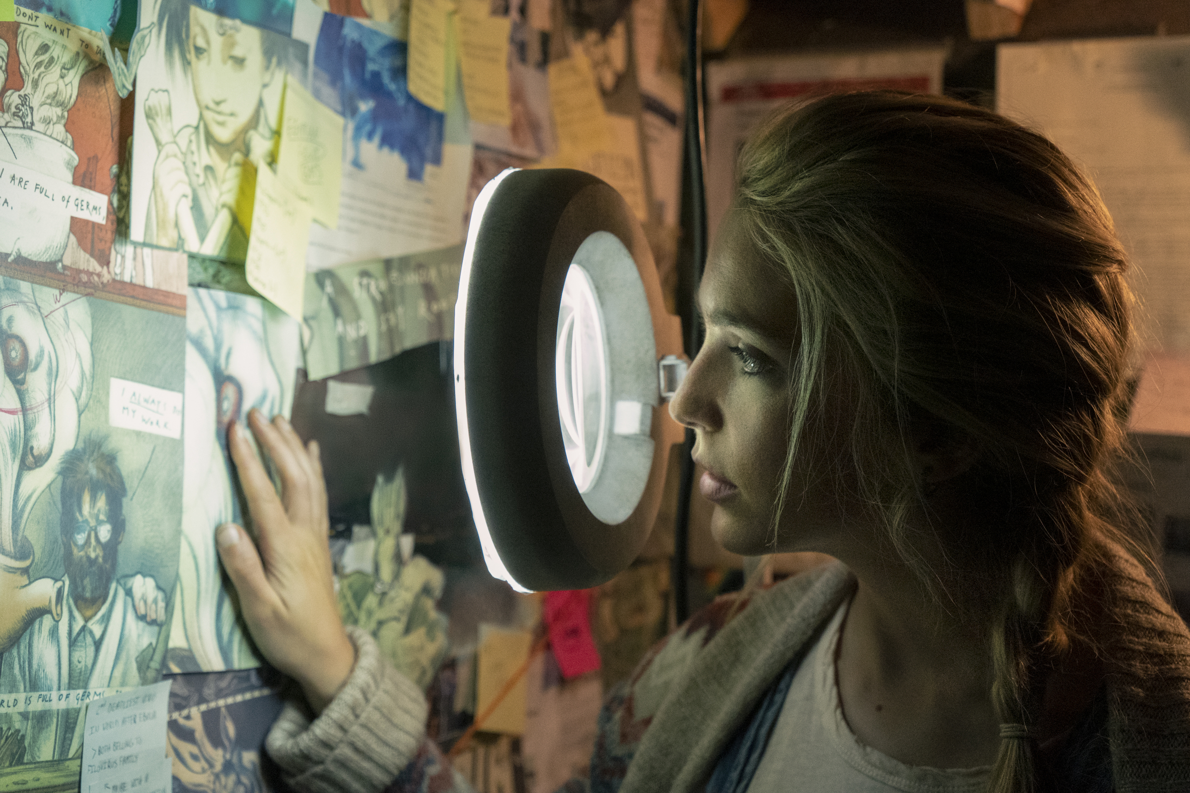 A character peers through a lit magnifier at a conspiracy board in Amazon's Utopia