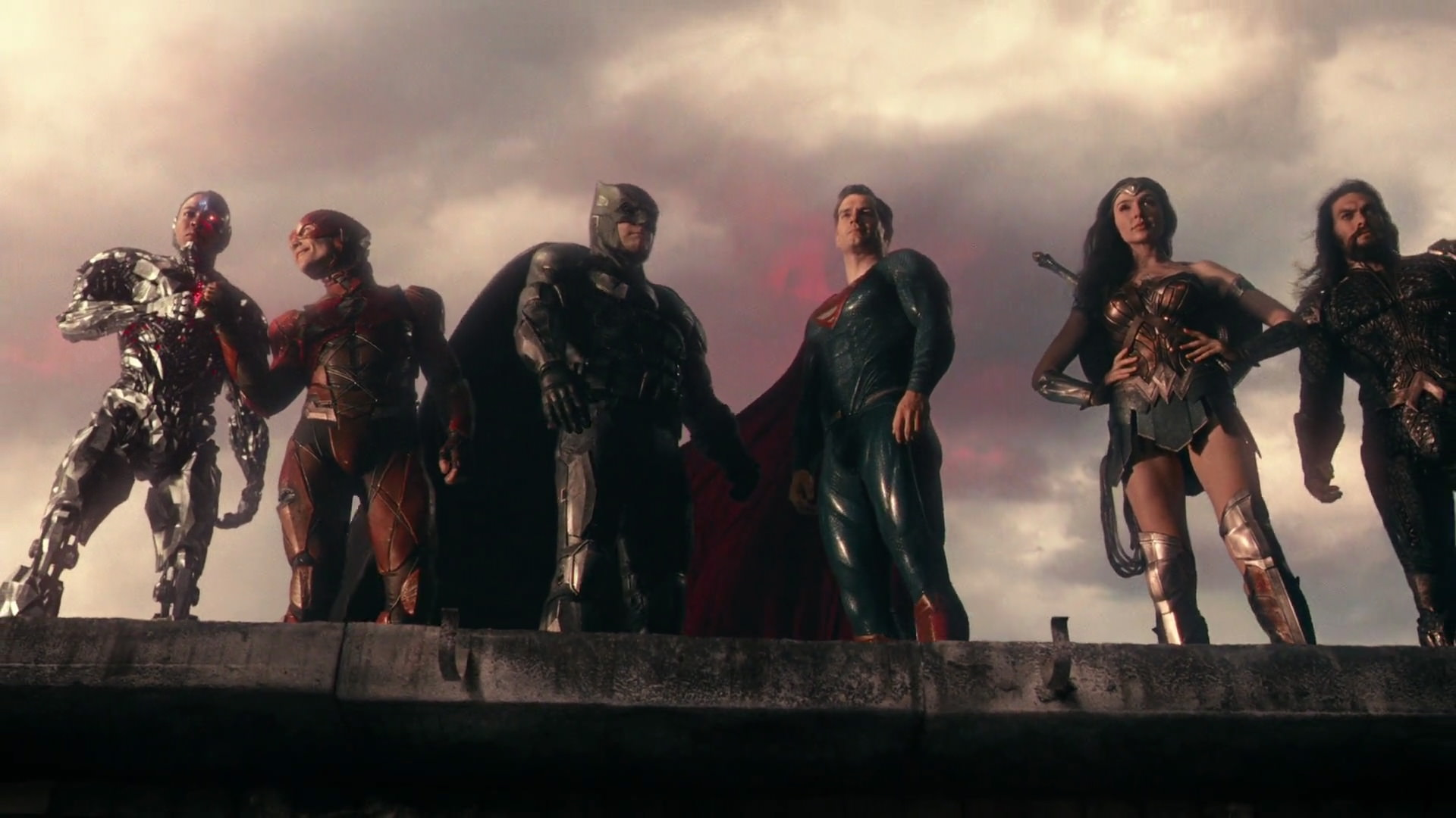 Cyborg, the Flash, Batman, Superman, Wonder Woman, and Aquaman stand on a ledge in in Justice League (2017).