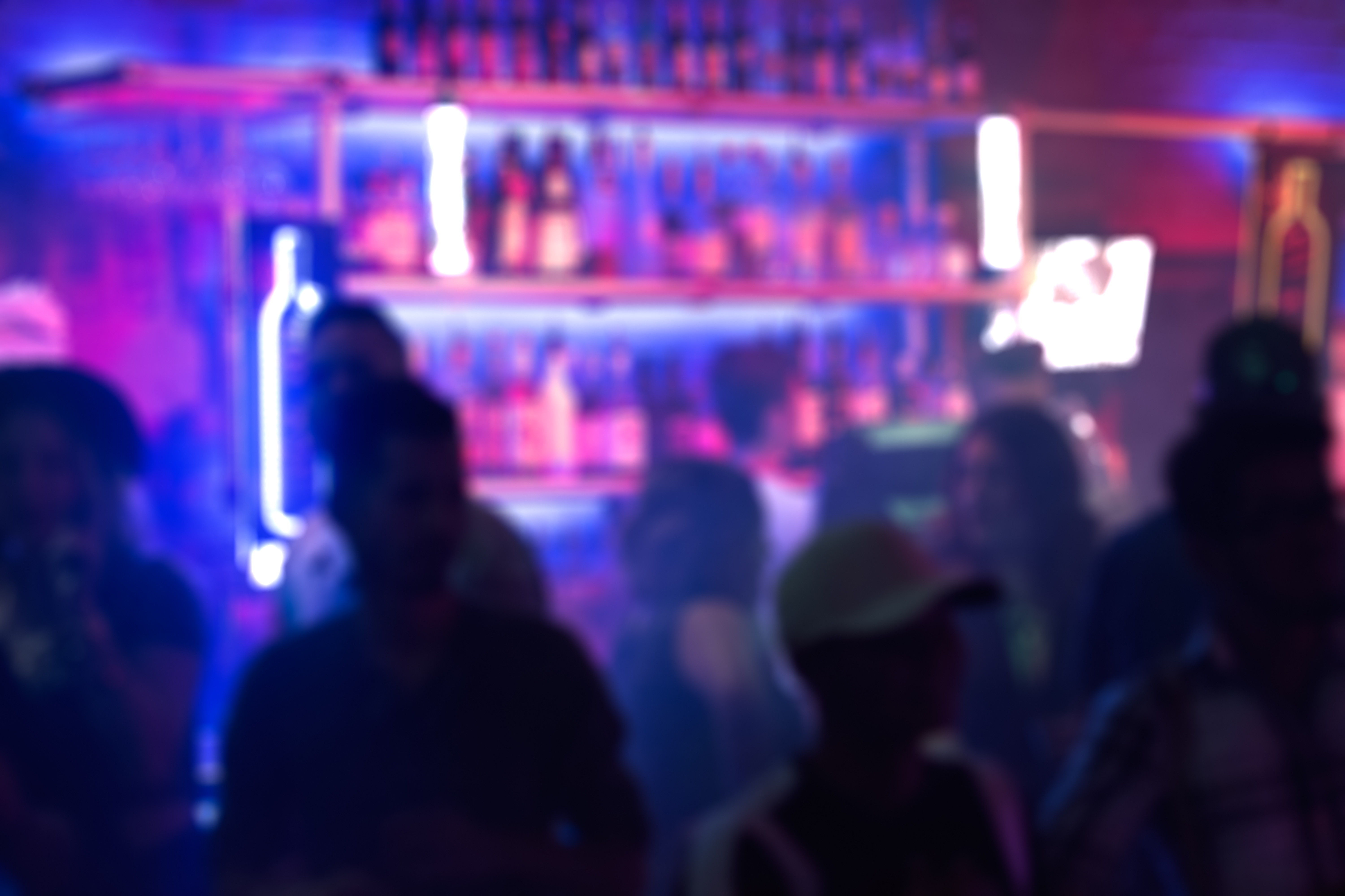 Blurry silhouettes of people cluster around a bar, with bottles of liquor visible in the background.