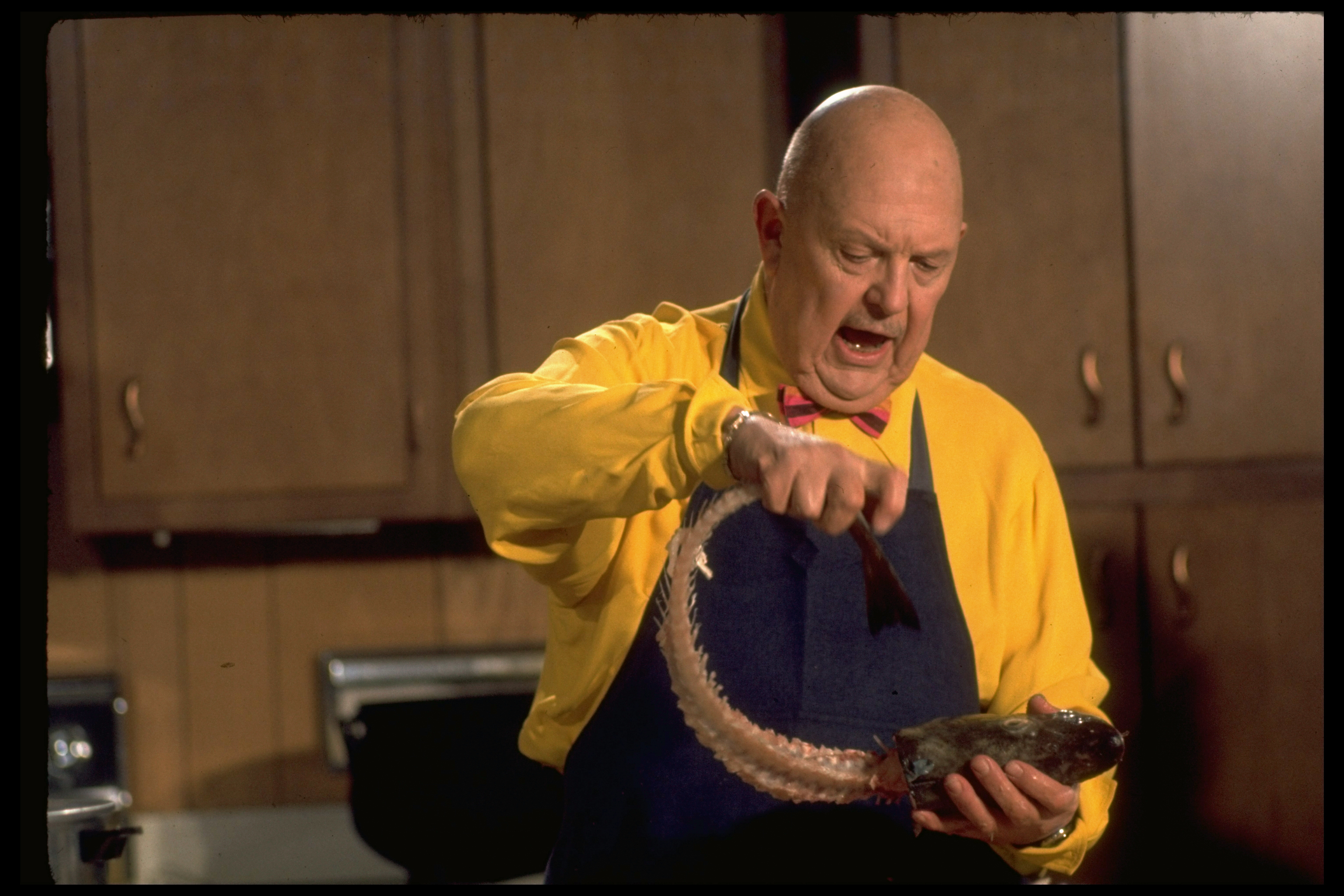 A man in a yellow shirt and apron holds a partially butchered fish