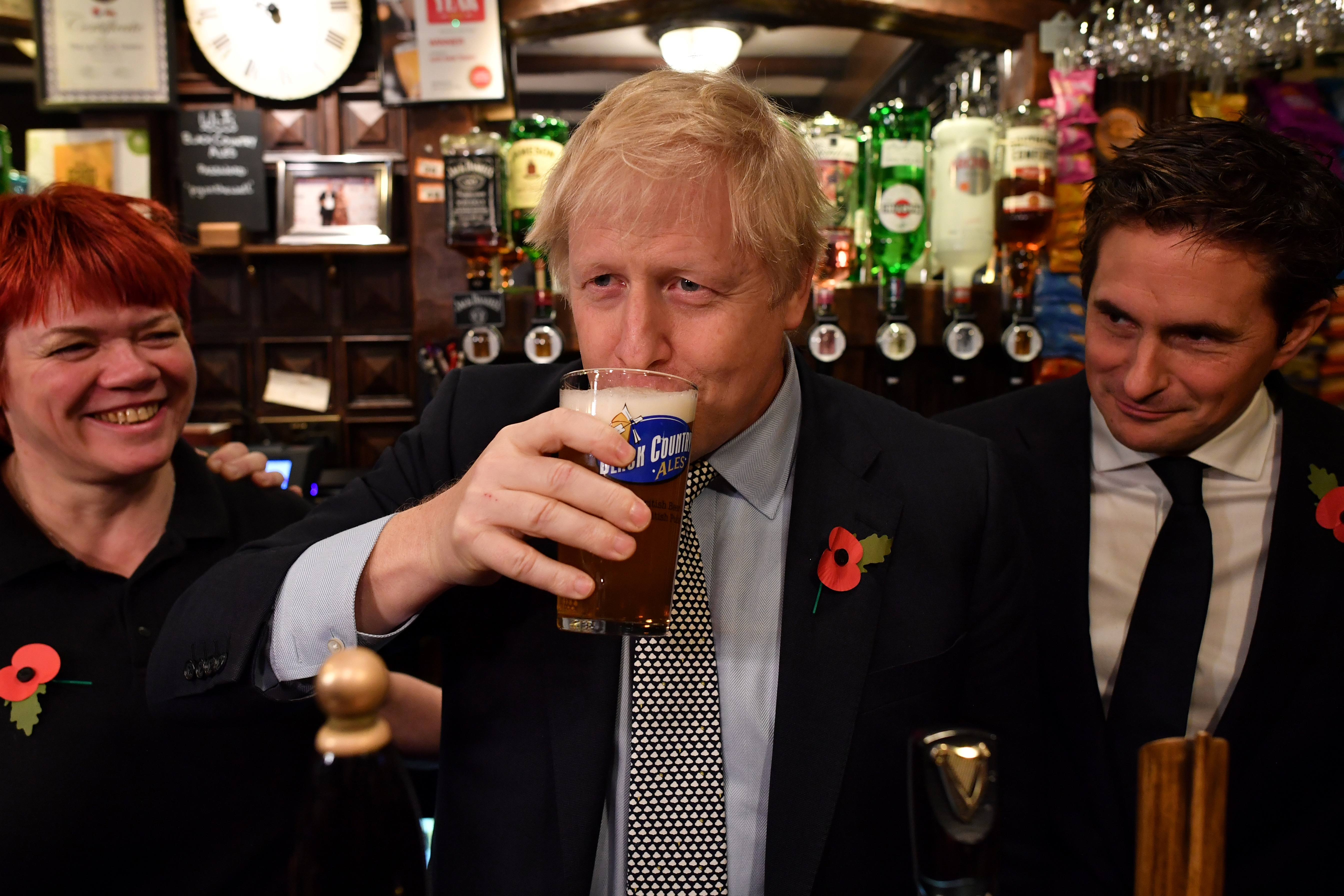Boris Johnson drinks a pint of beer at a Wolverhampton pub flanked by bar staff