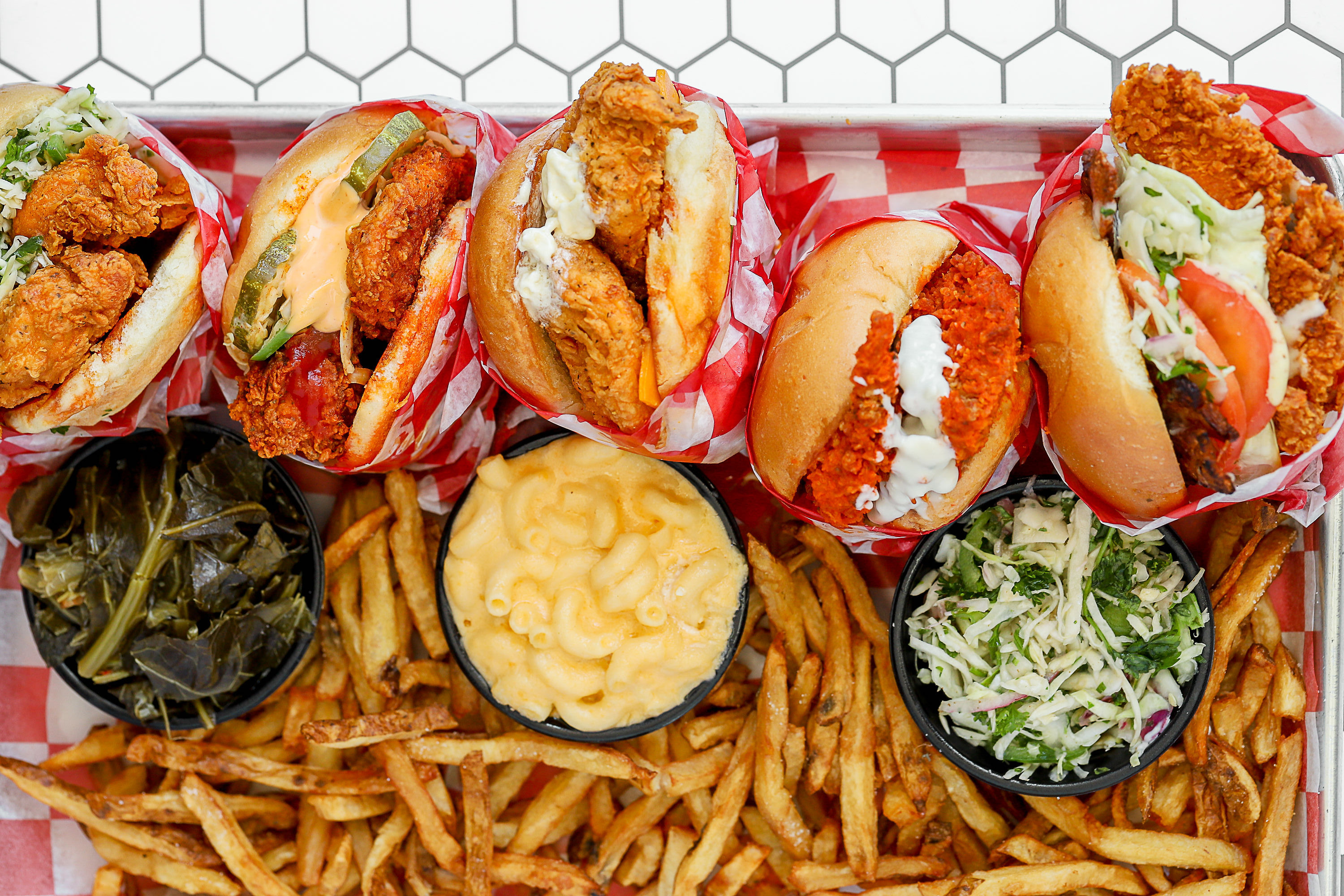 Five fried chicken sandwiches are surrounded by fries and other sides