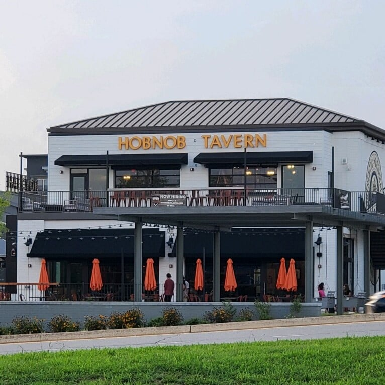 The two-story Alpharetta location of Hob Nob Neighborhood Tavern, a white building with black trim and roof, two patios, and orange umbrellas on the ground floor patio