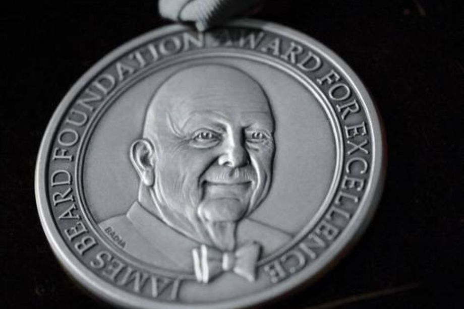 A silver medal with a man's face on it.